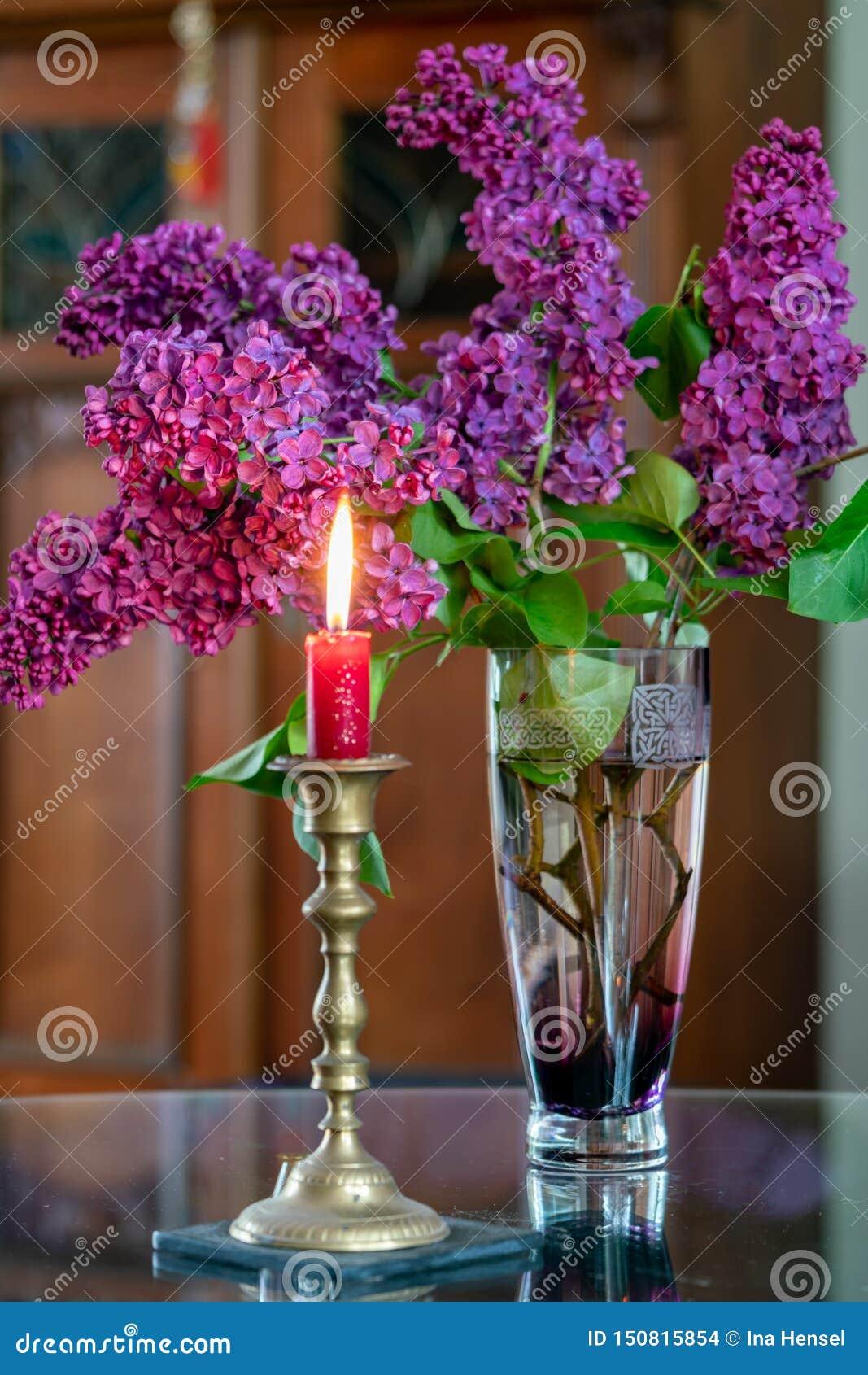 Diseño interior con una vela roja ardiente y un florero