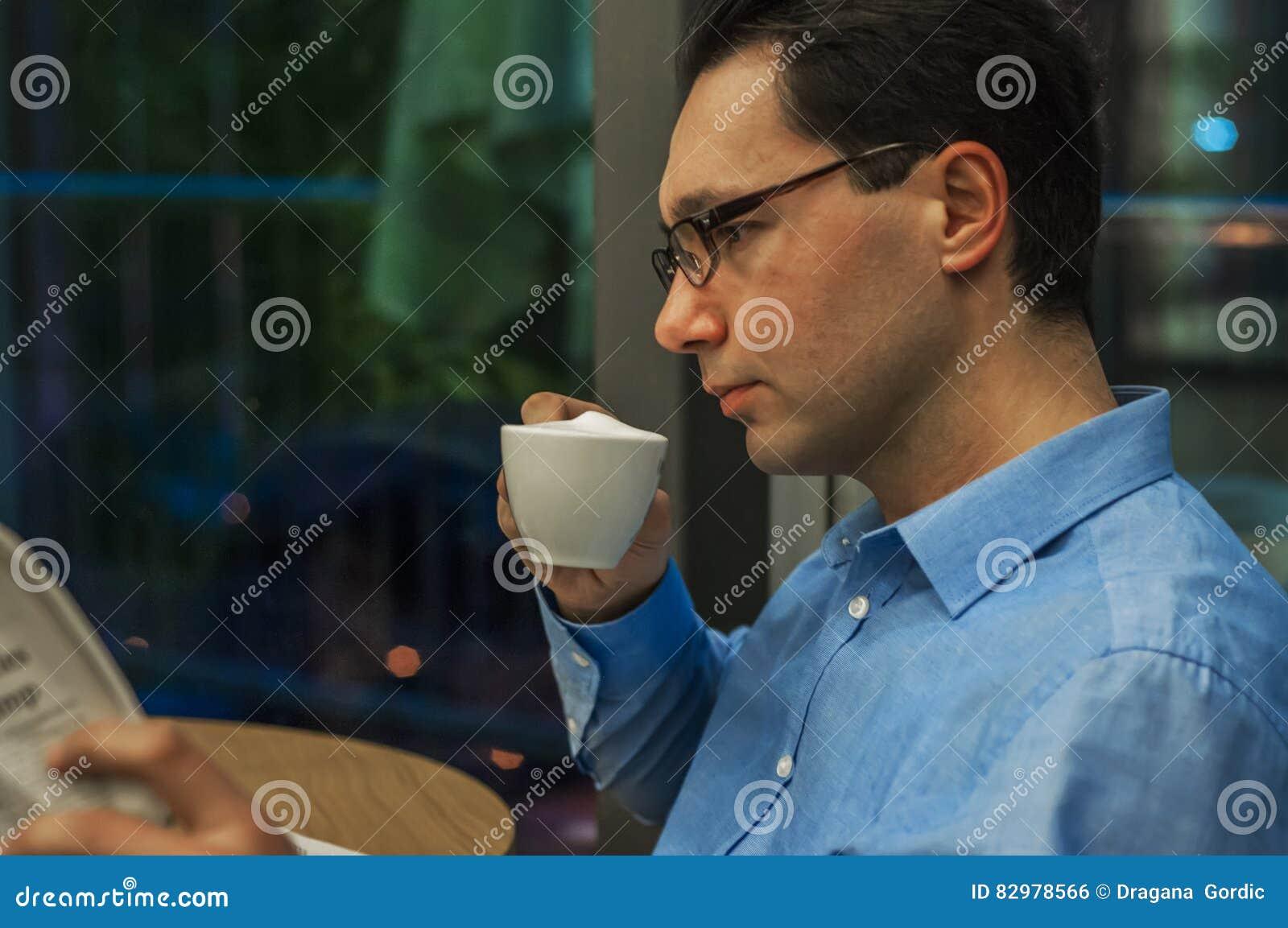 Disfrutar de la época libre para el café y un ciertas noticias periódico de la lectura del hombre de negocios mientras que bebe u