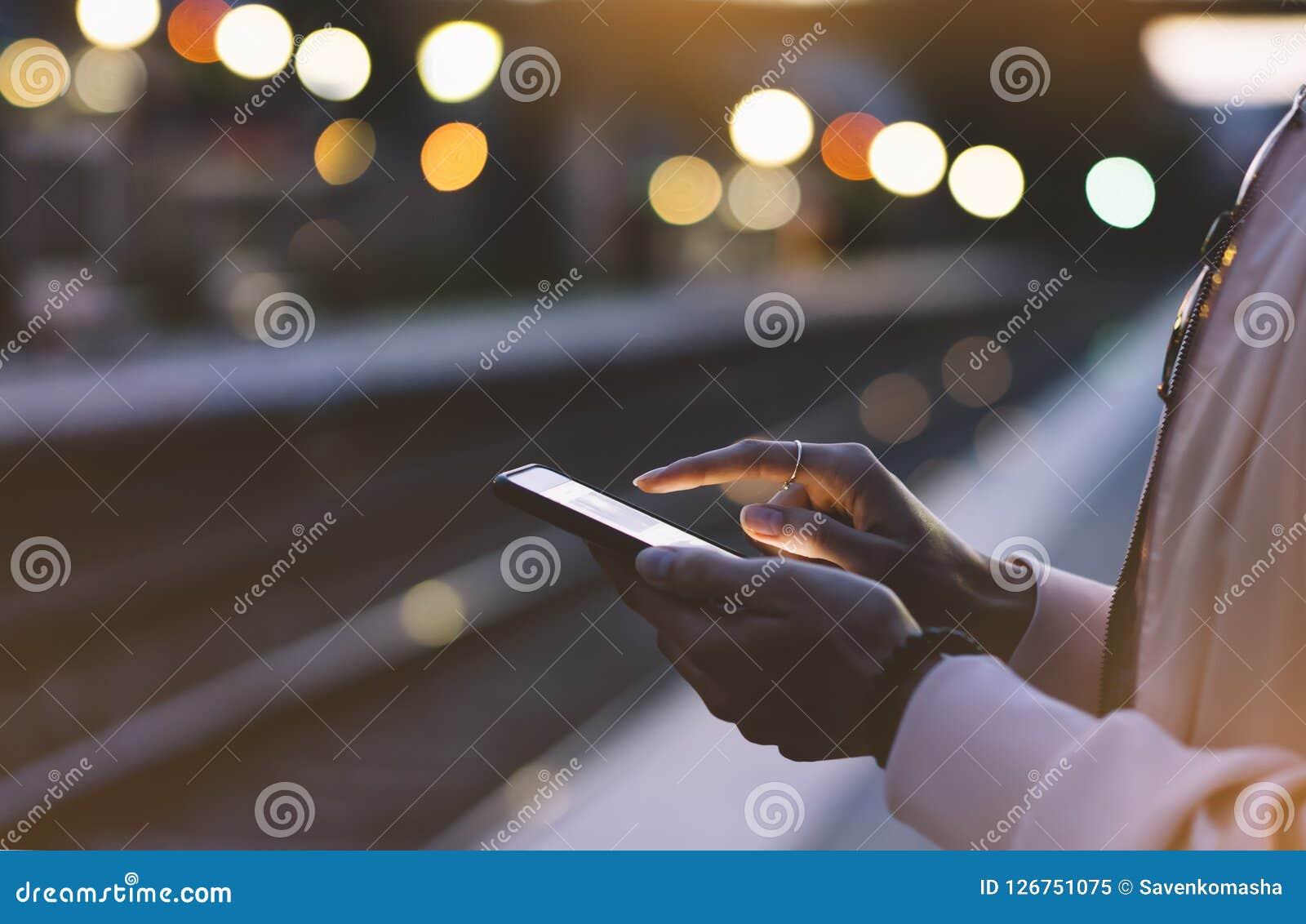 Disfrutar de viaje Mujer joven que espera en la plataforma de la estación en el tren móvil eléctrico de la luz del fondo usando e