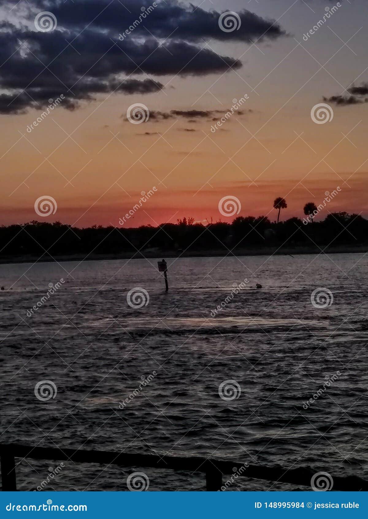 Disfrute de la puesta del sol rosácea hermosa en la playa en la Florida