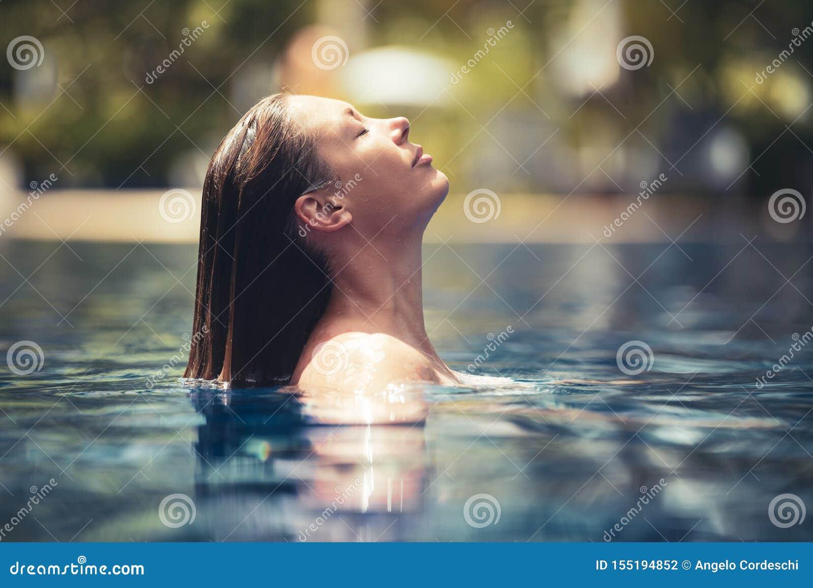 Disfrute del verano Mujer que se relaja en el agua de la piscina