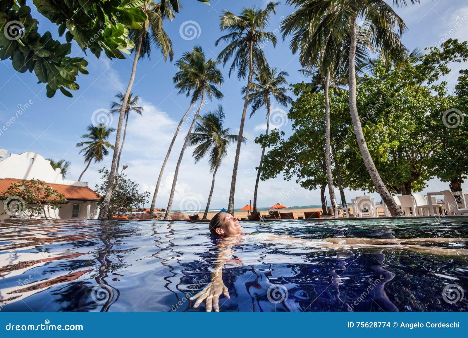 Disfrute del verano tropical Mujer que se relaja en el agua de la piscina