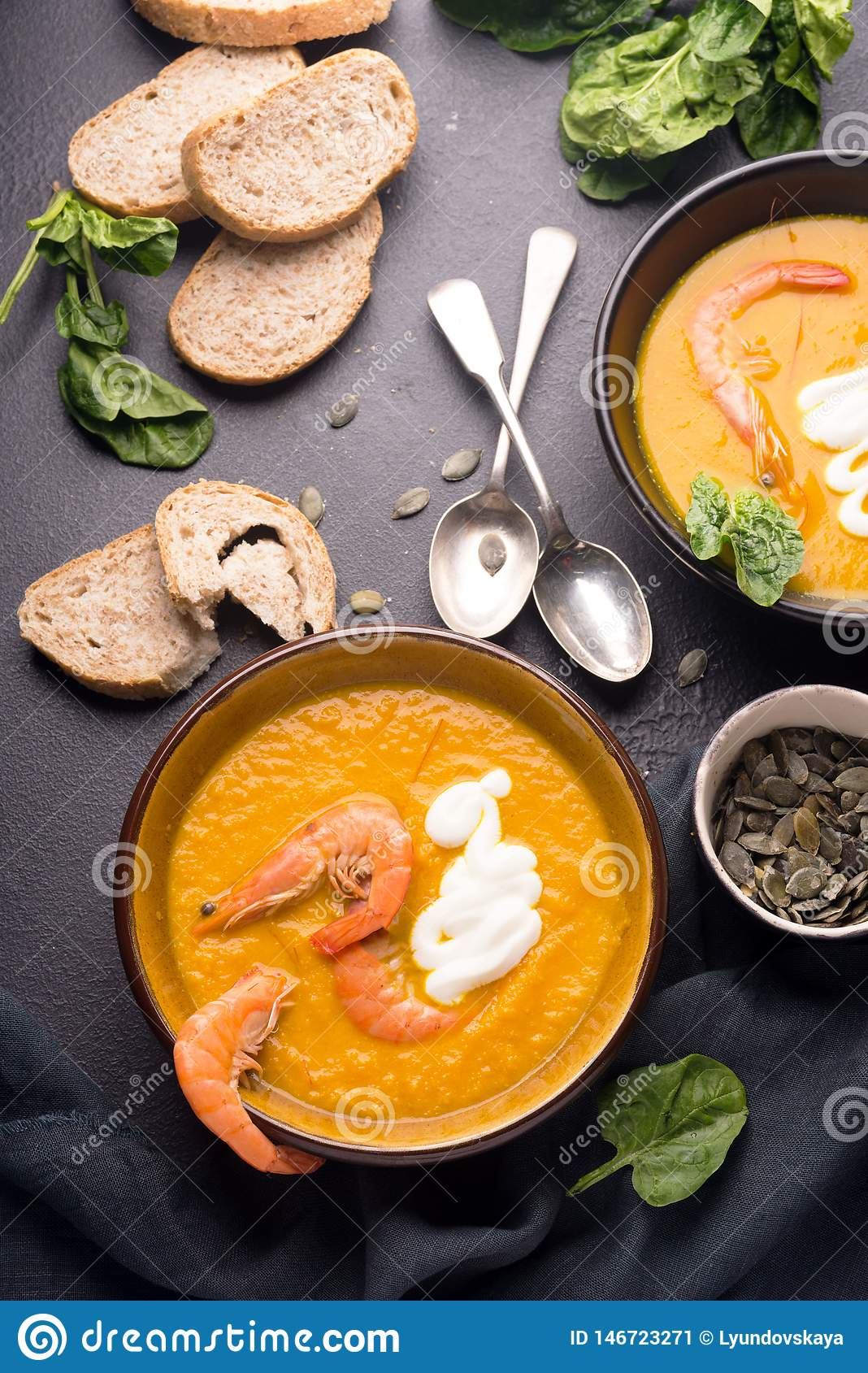 2 dishes of orange pumpkin soup on a black table. Three red shrimps decorate the soup.