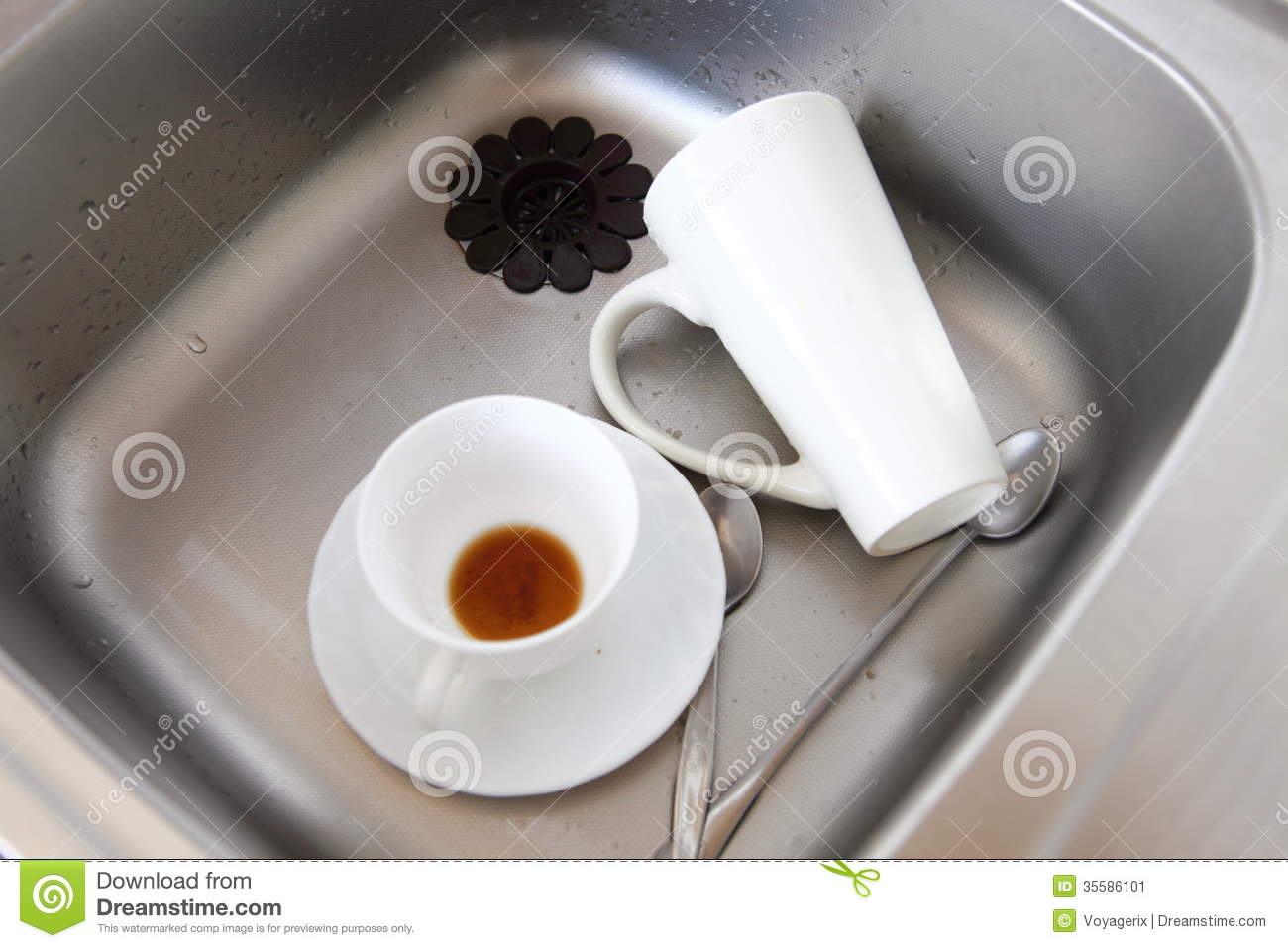 Washing up. White coffee cups in the kitchen sink.