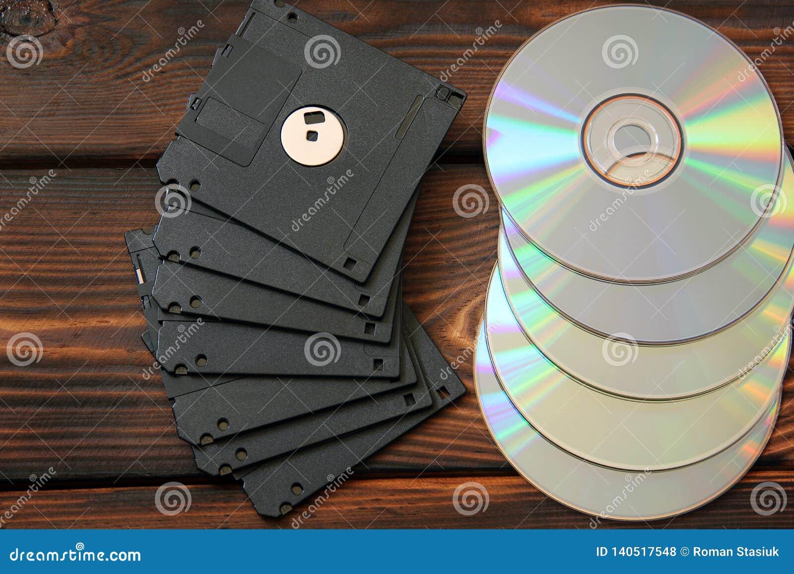 Disketter och skivor på träbakgrund