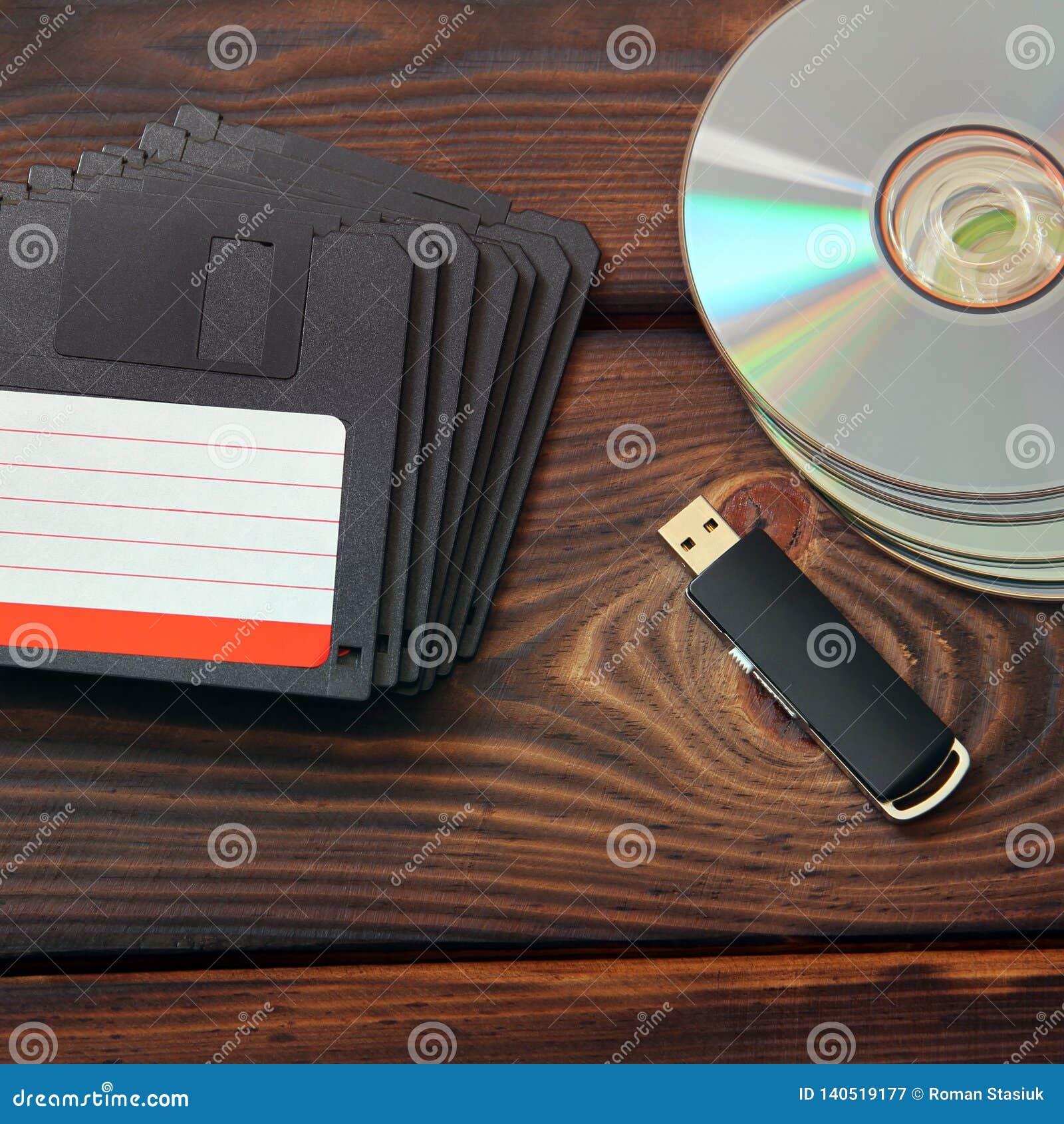 Diskettes, memoria USB y discos en un fondo de madera