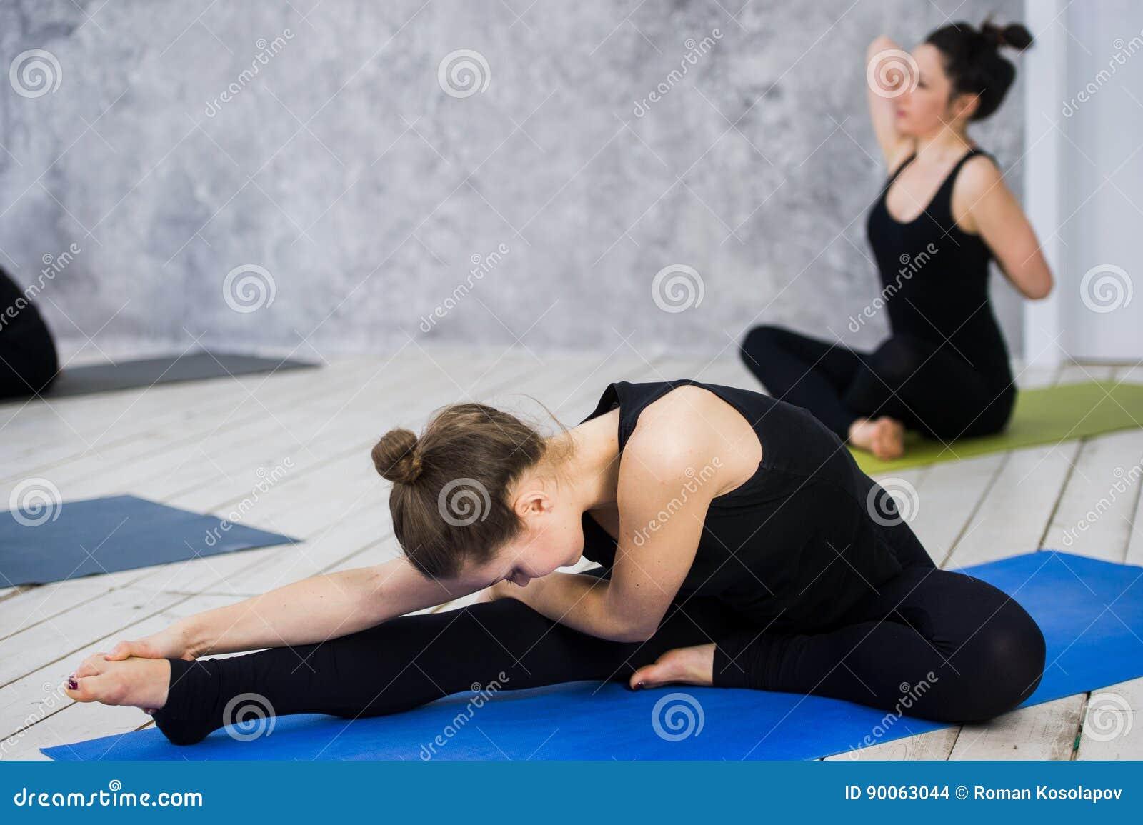 Disparado das jovens mulheres que aquecem-se antes da sessão da ioga Os jovens que sentam-se na esteira do exercício na ioga clas