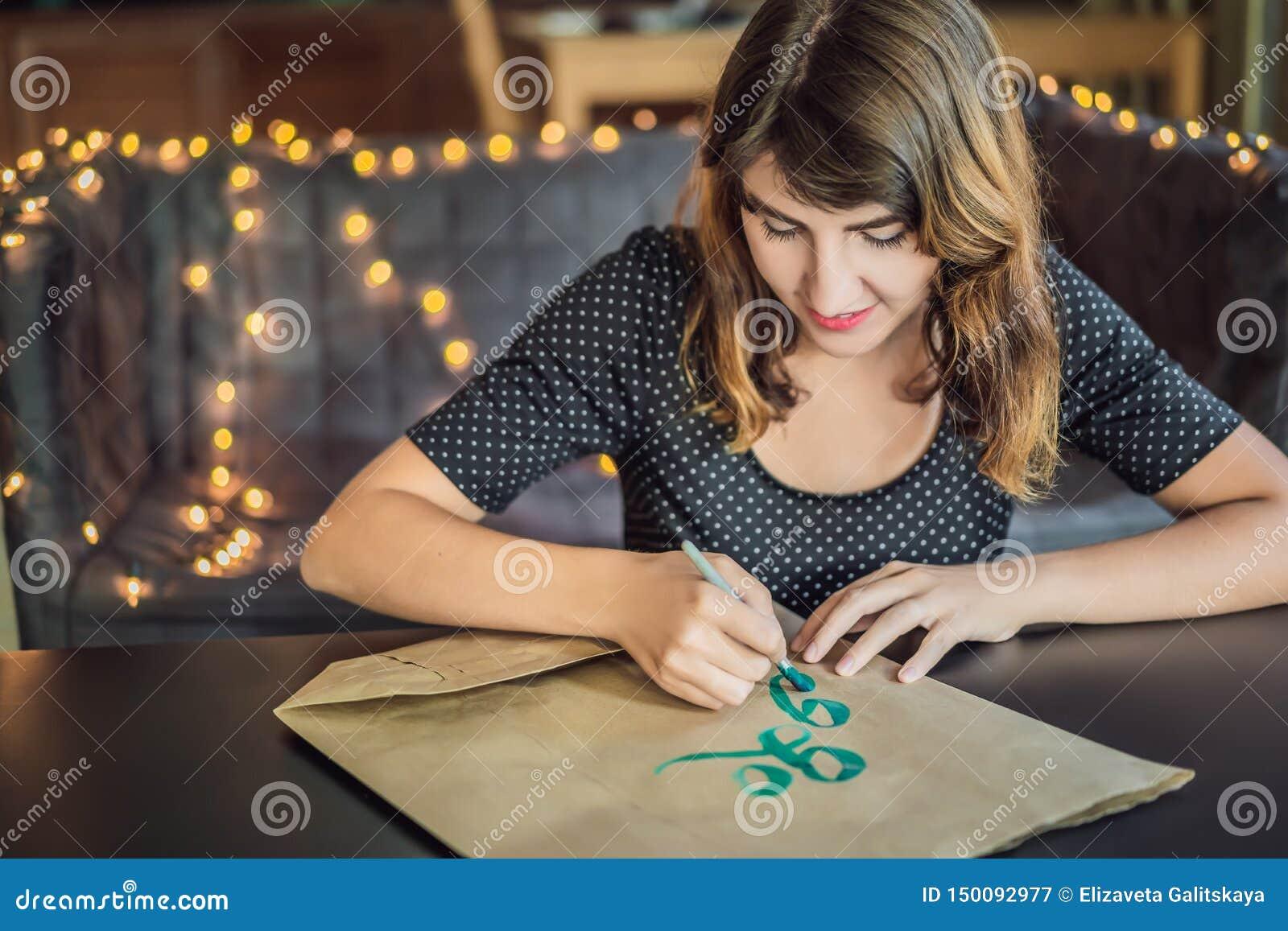 Disparaissent le vert Le calligraphe Young Woman ?crit l expression sur le livre blanc Inscrire les lettres d?cor?es ornementales