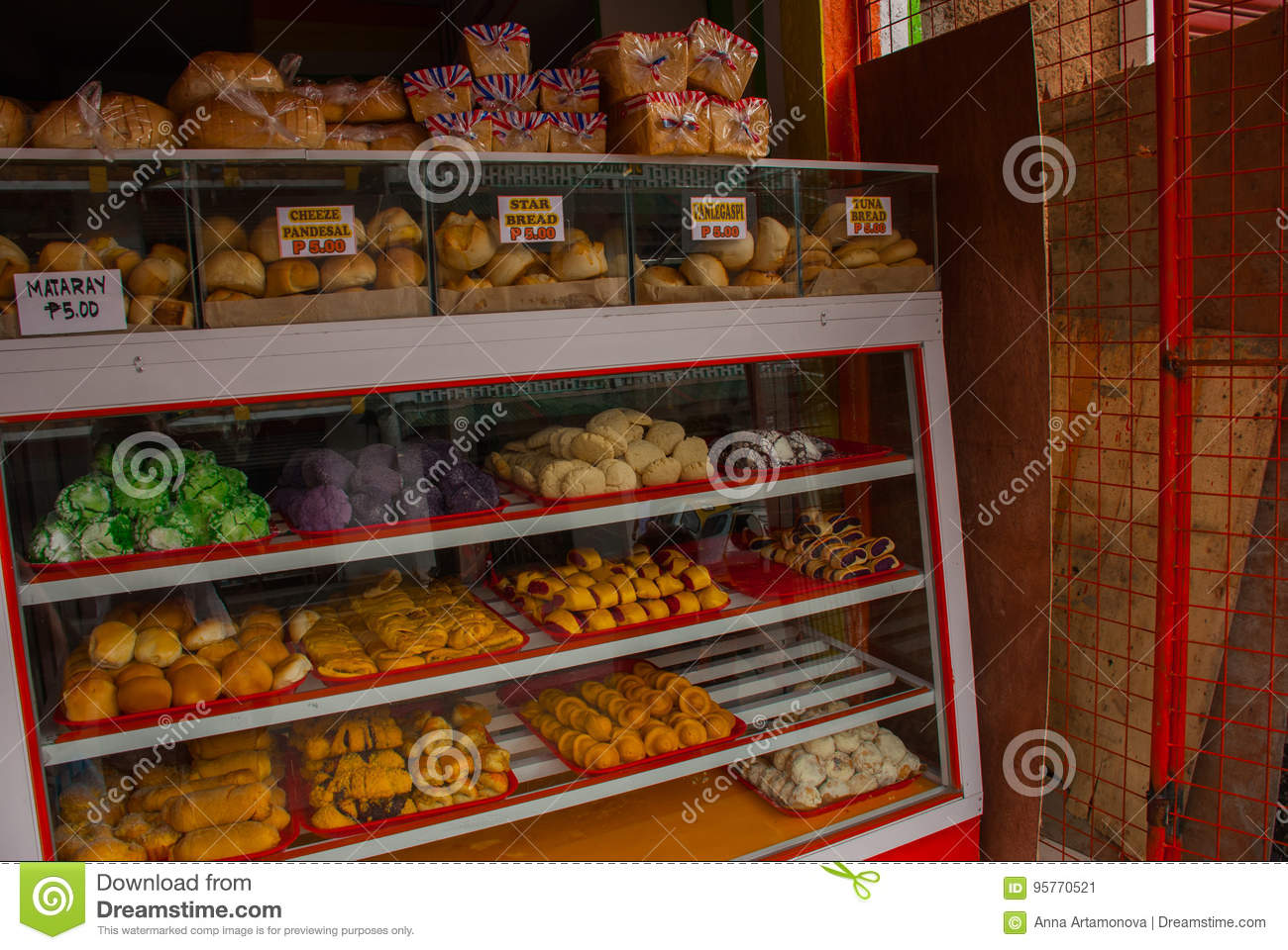 Display window of a bakery and pastry shop of with variety of baked goods, breads, donuts, puff pastry, closeup. Philippines.