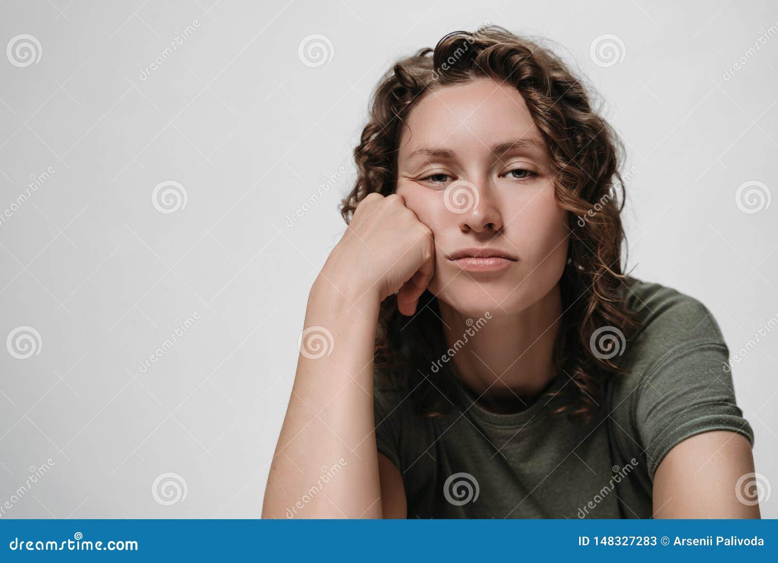 Displeased утомляло сонную курчавую женщину, подпирающ его щеку, смотря пробурено