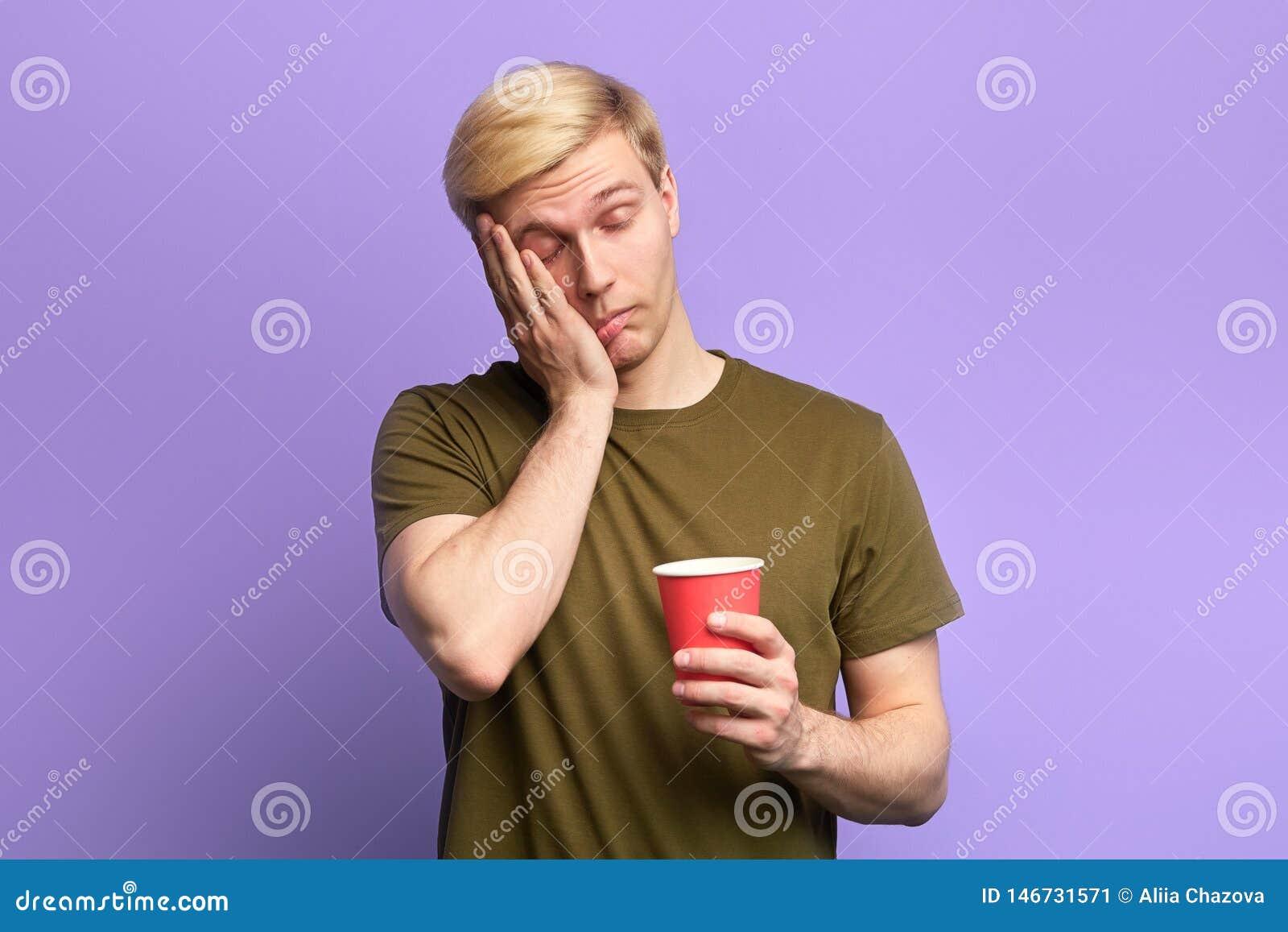 Displeased утомляло сонный человека с напитком в устранимой пластиковой красной чашке