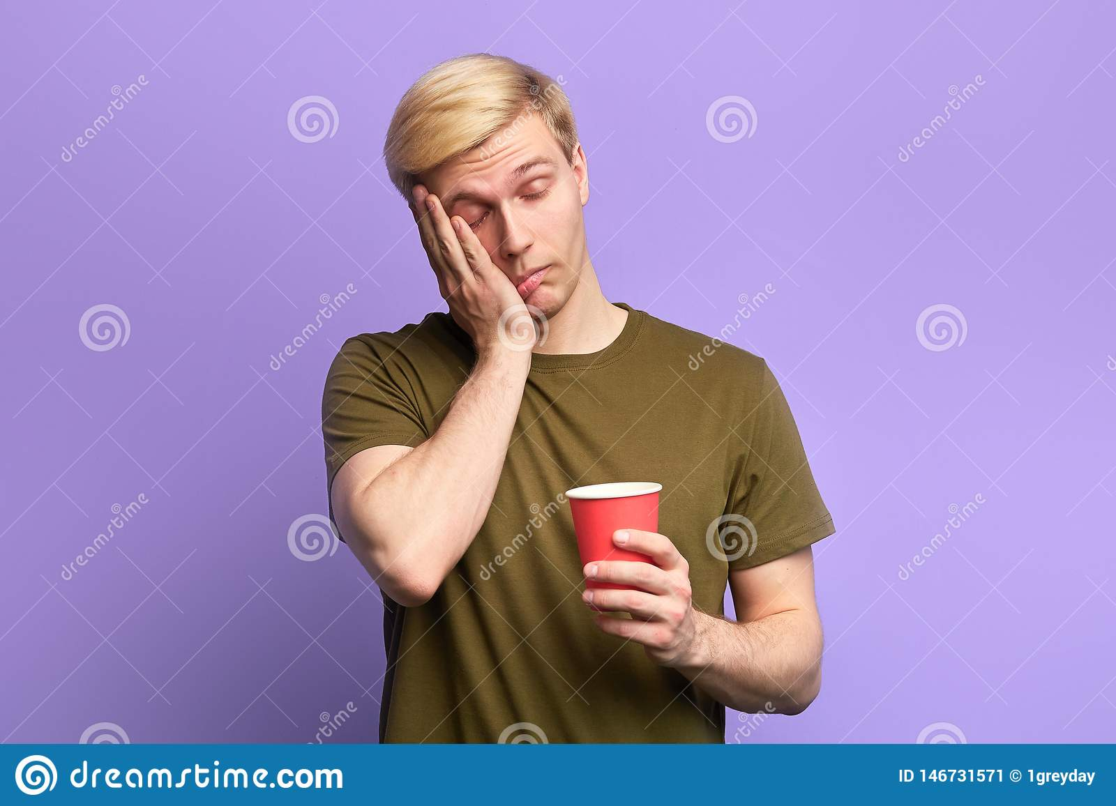 Displeased tired sleepy man with beverage in disposable plastic red cup
