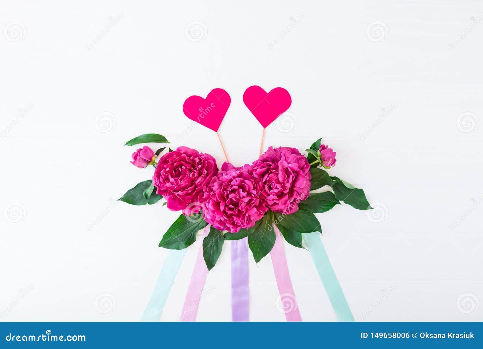 Disposi??o com composi??o das flores da pe?nia, fitas e dois cora??es em um fundo branco Amor, casamento O modelo floral do Valen