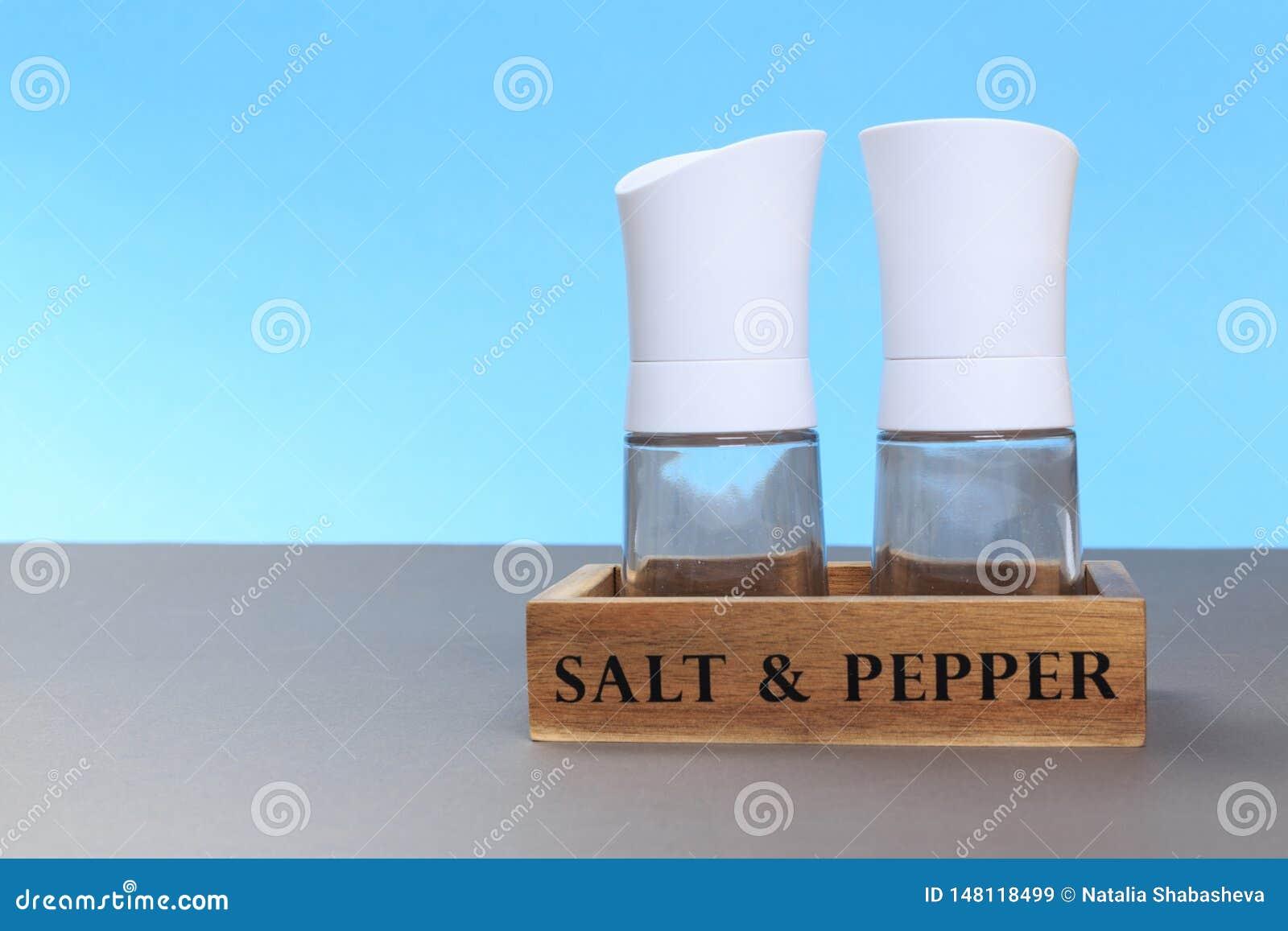 Dispositif trembleur de sel et de poivre sur le conseil gris et un fond bleu