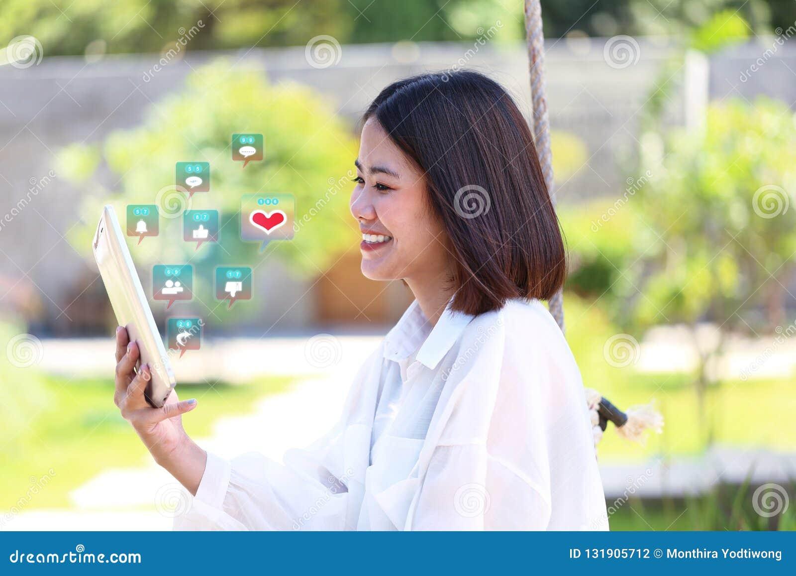 Dispositivo elegante del inconformista de la muchacha de la mano de la tableta feliz de la tenencia con hologra
