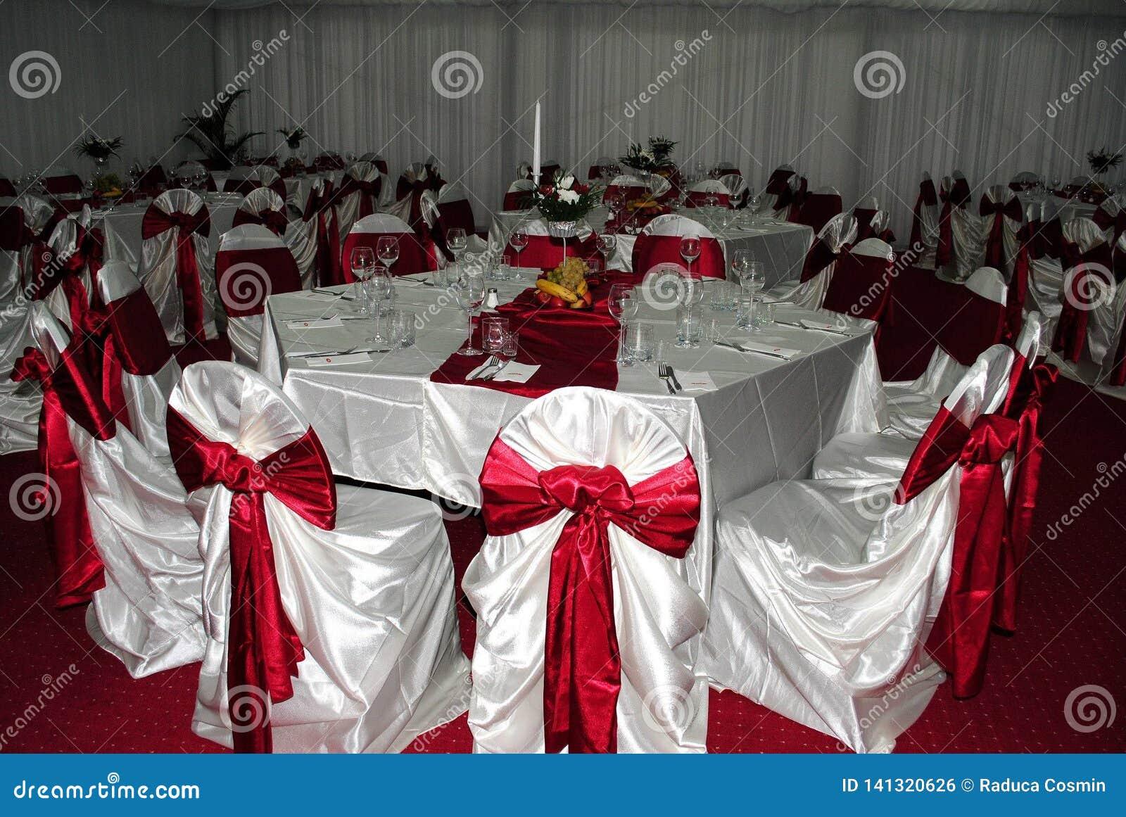Disposizione di nozze con le sedie bianche e rosse che aspettano gli ospiti di g