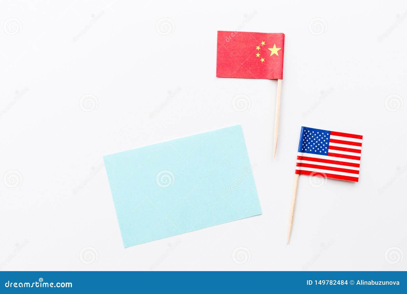Disposizione piana creativa di vista superiore della Cina e bandiera di U.S.A., modello e spazio della copia su fondo bianco nell