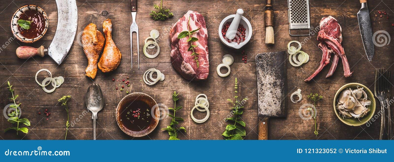 Disposizione piana di varia griglia e della carne del bbq: coscie di pollo, bistecche, costole dell agnello con gli utensili d an