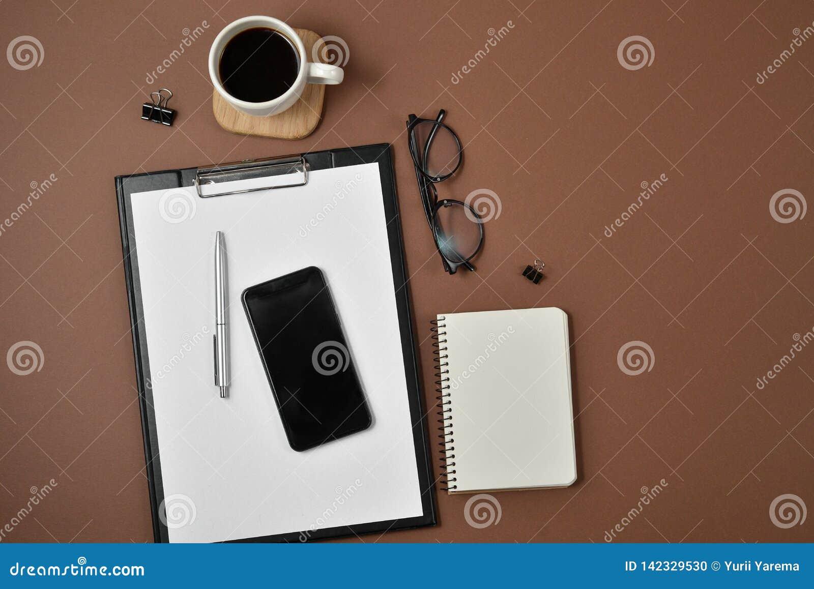 Disposizione piana, scrittorio della tavola dell ufficio di vista superiore Area di lavoro con il bordo di clip in bianco, taccui