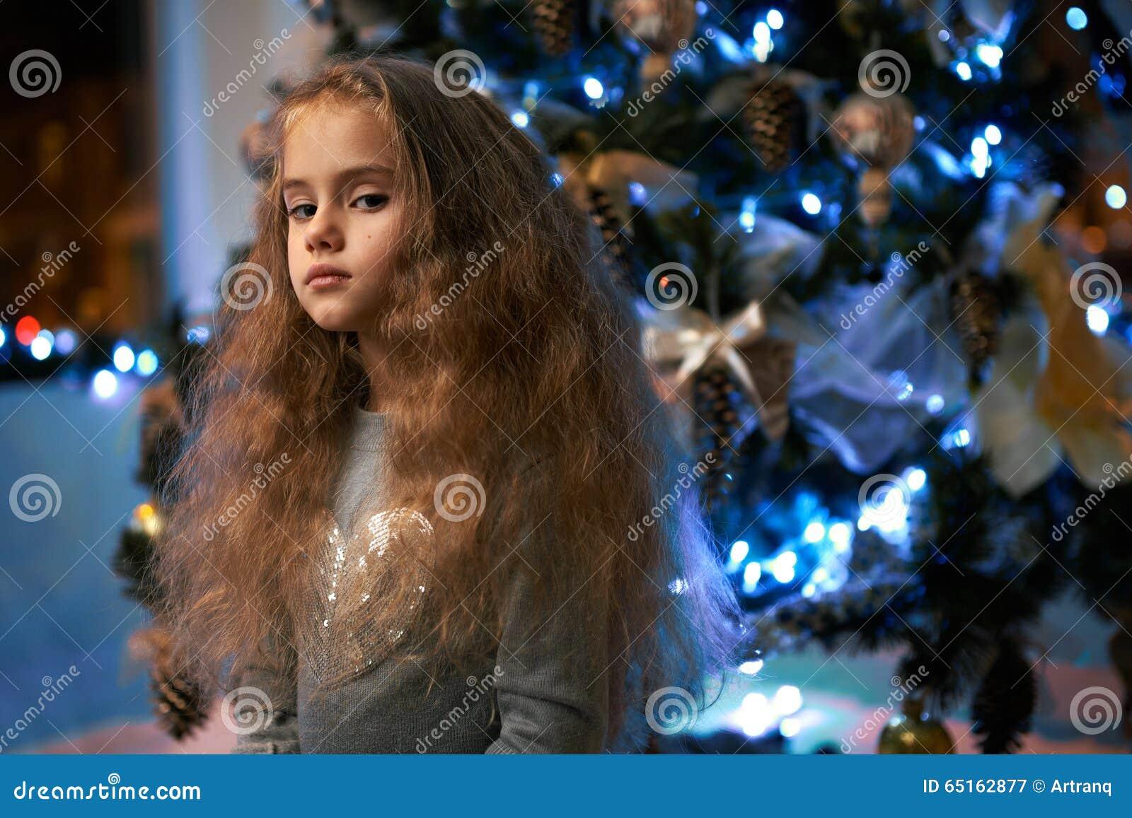 Disprezza la bambina vicino all albero di Natale