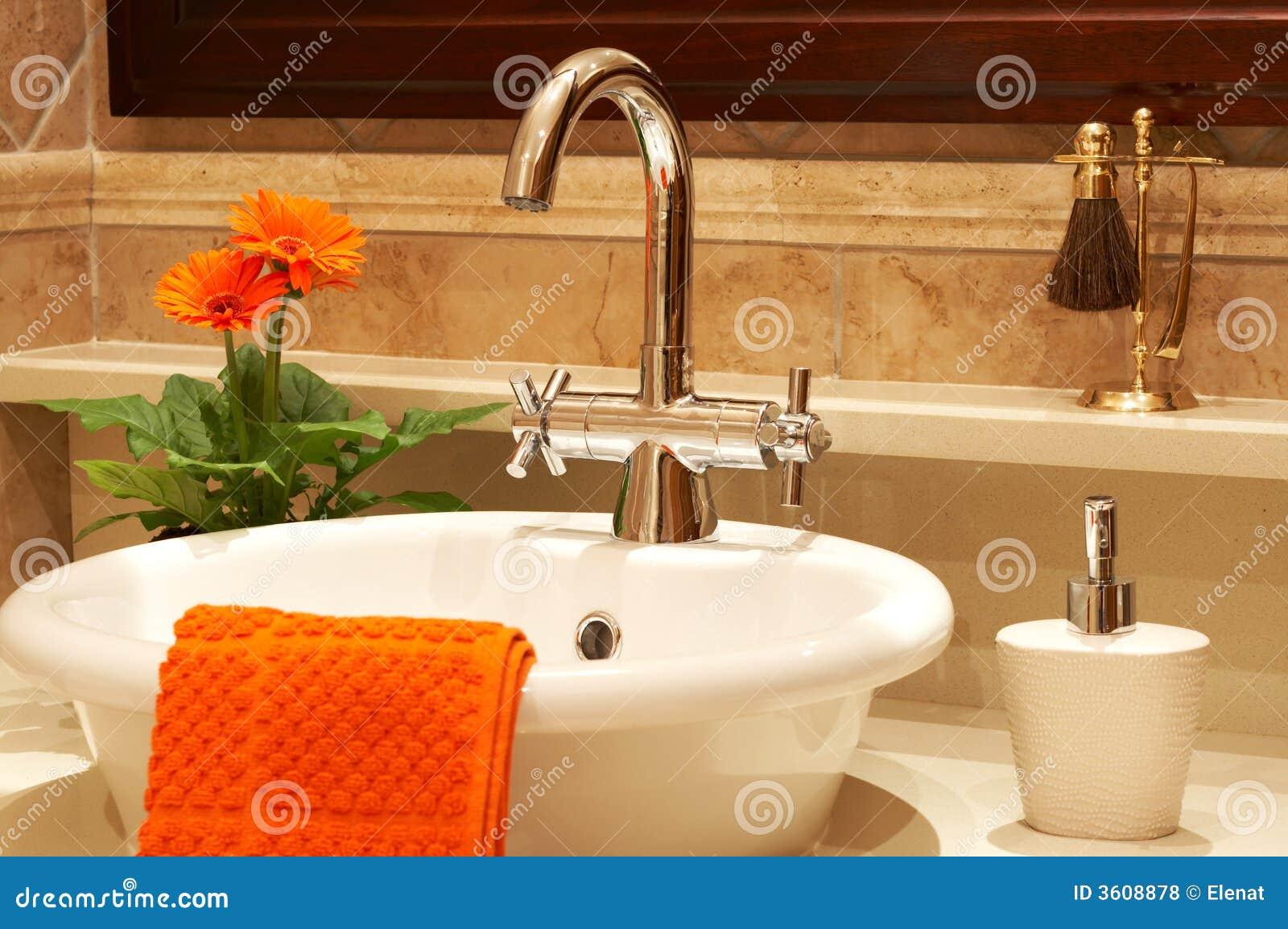 Dissipador bonito em um banheiro com toalha nela e em uma flor. O foco  #C63505 1300 954