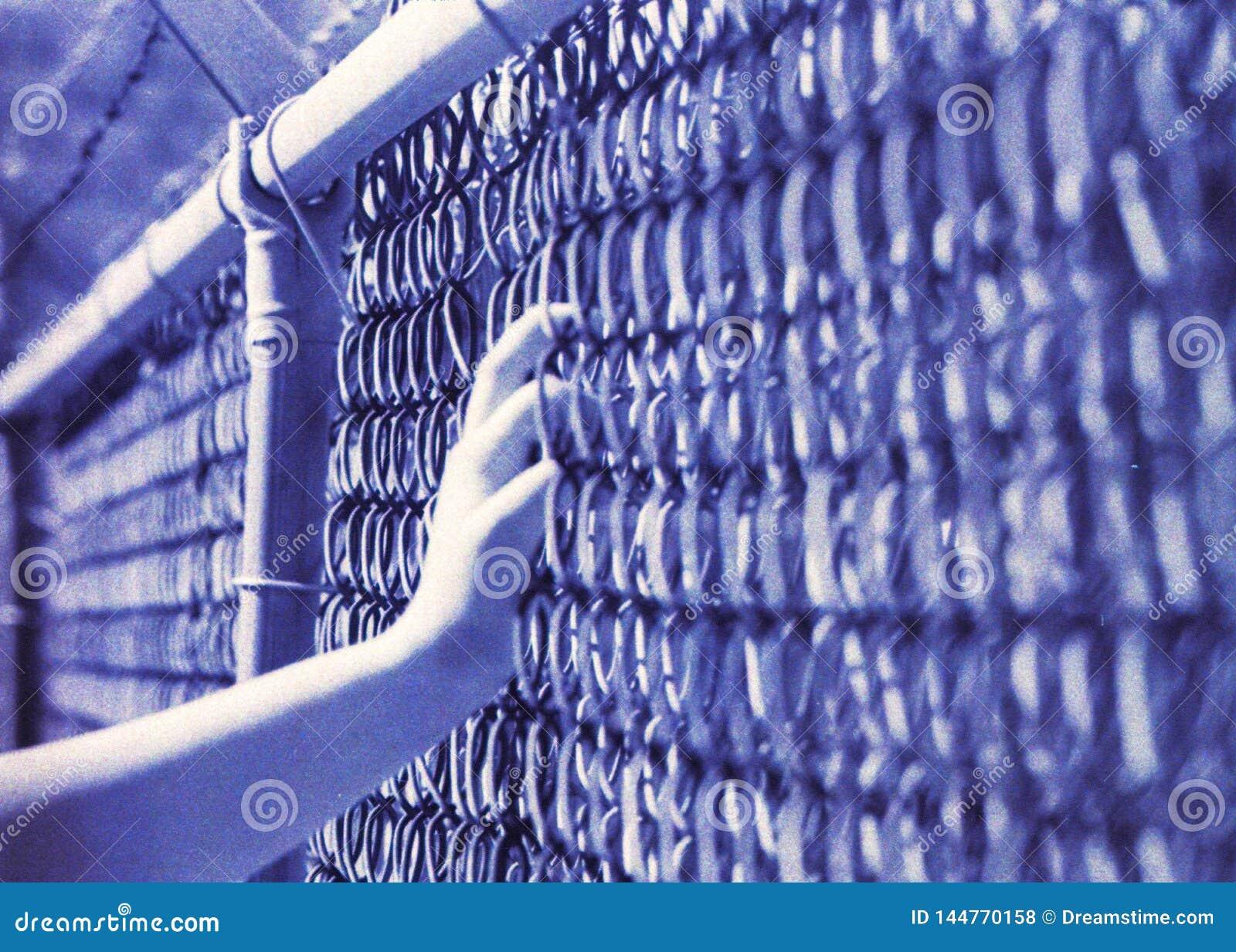 Distorção do filme de uma mão em uma cerca