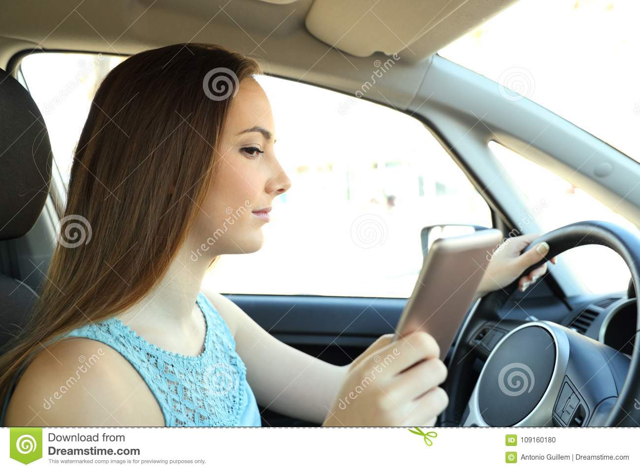 Distracted driver reading phone message driving a car