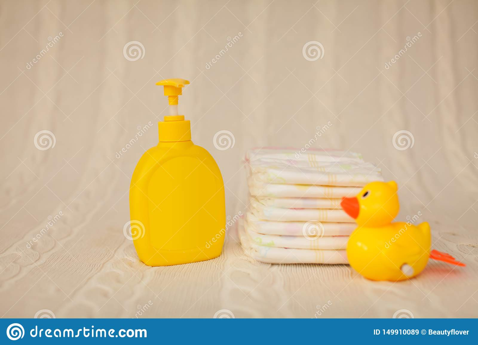 Distributeur en plastique jaune avec du savon liquide et une pile de serviettes brunes sur une couverture beige au foyer sélectif