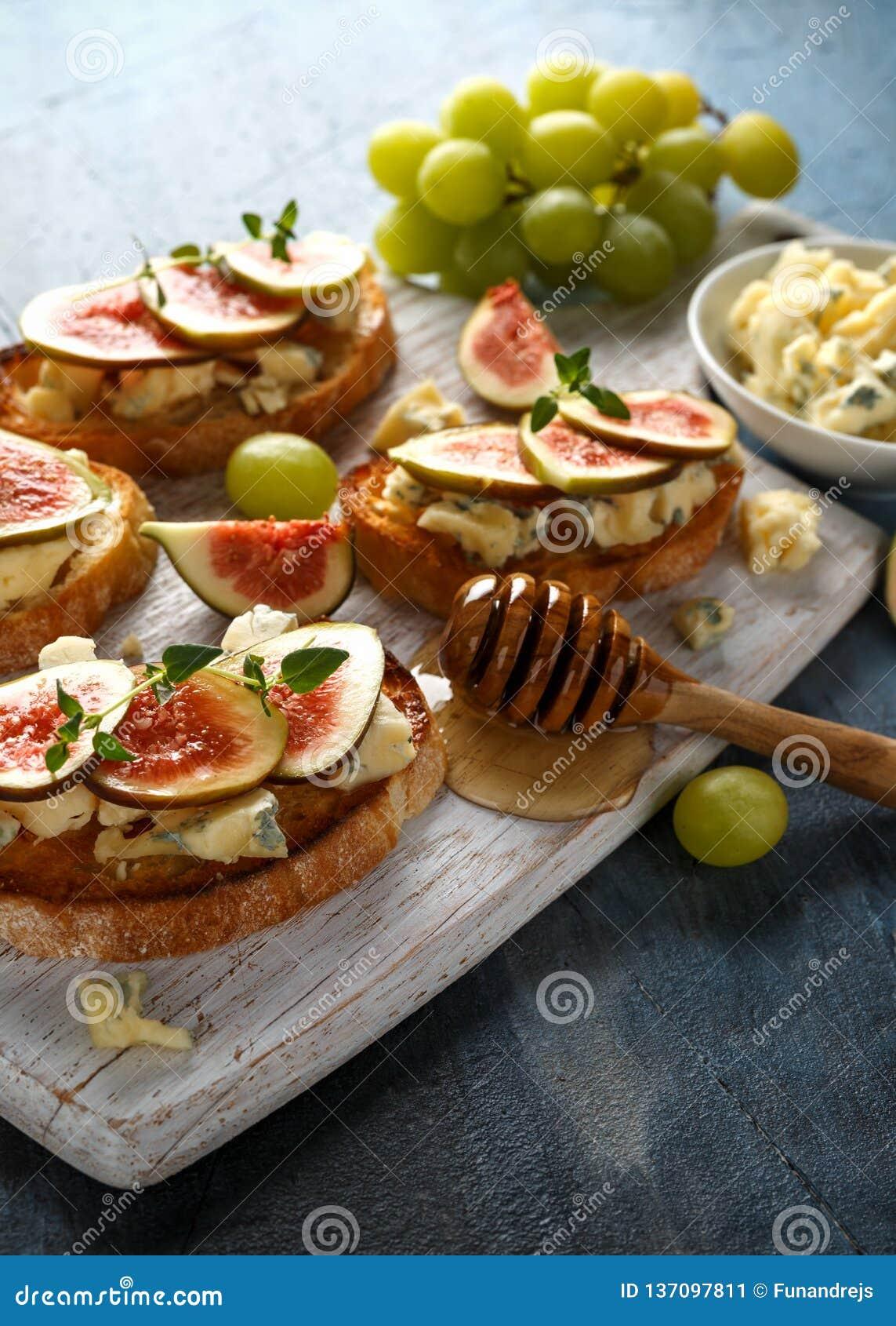 Dit Fig. en Gorgonzola-tartines, toost, bruschetta gemotregend met honing op witte houten raad