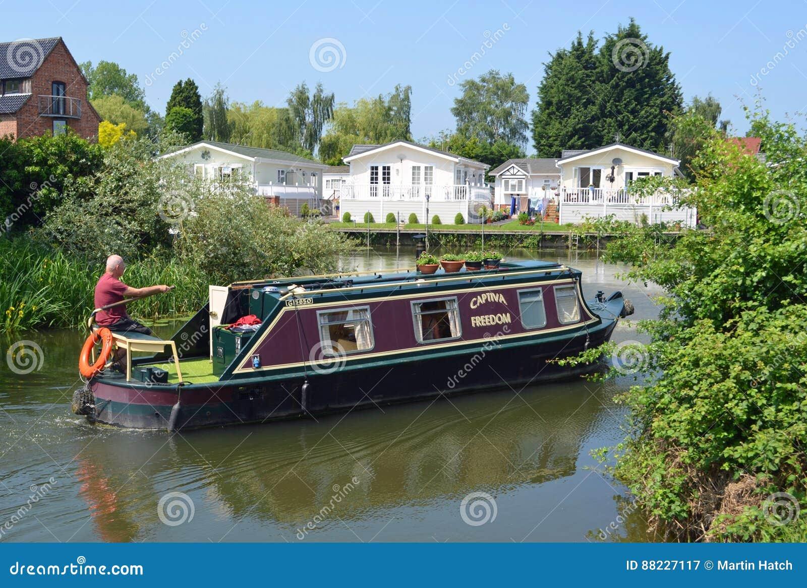 Ditional restringe la barca sul fiume Ouse con le casette della riva del fiume a Buckden Marina Cambridgeshire