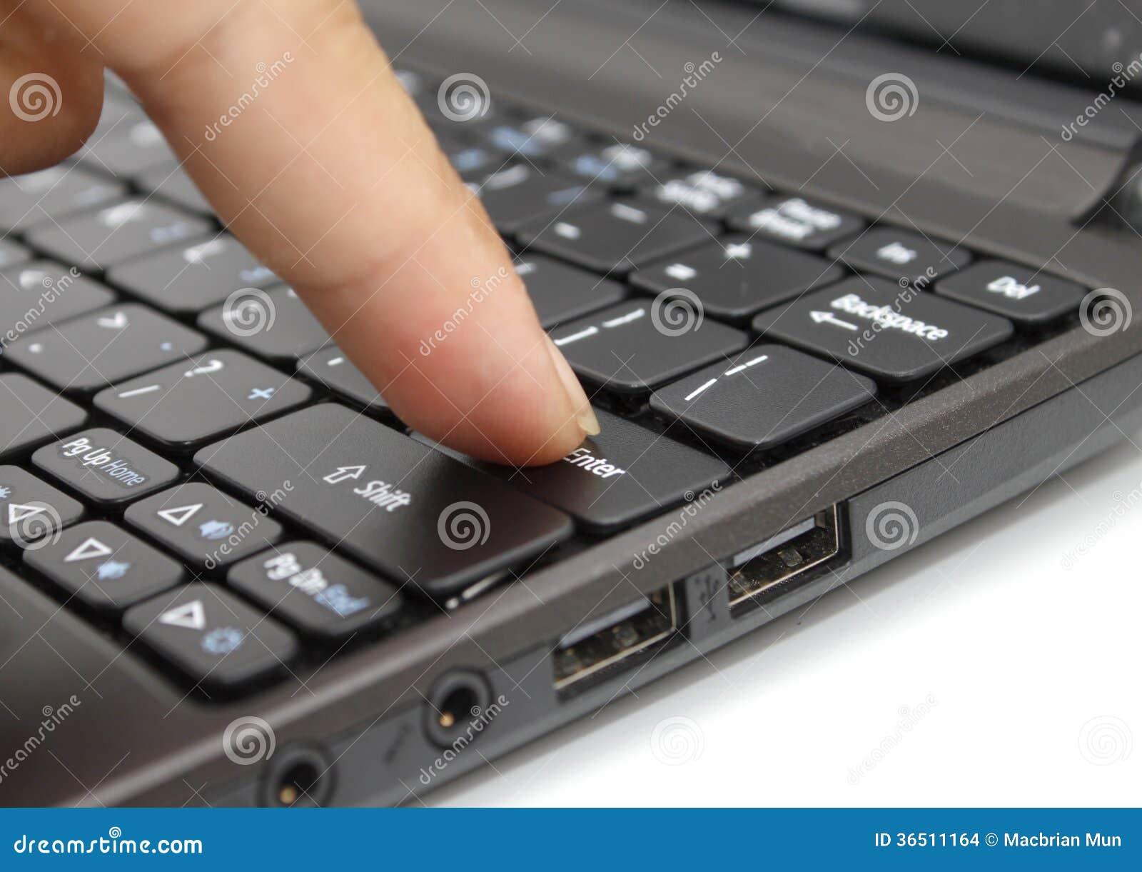 Dito che preme il tasto di introduzione su una tastiera
