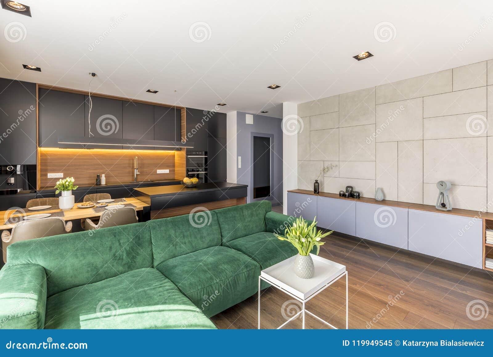 Divan de velours placé dans l intérieur de salon et de cuisine de l espace ouvert avec les fleurs fraîches, la table de salle à m