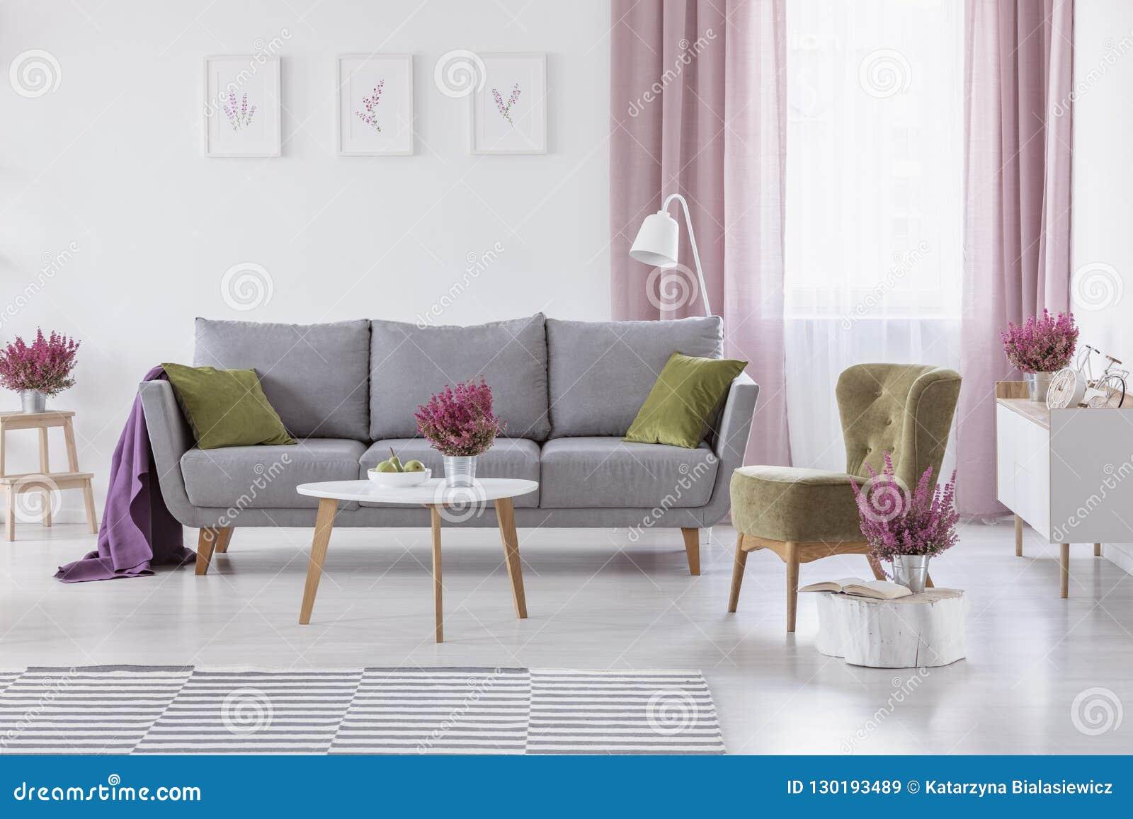 Divano Rosso E Grigio divano grigio con i cuscini verdi e coperta porpora in foto