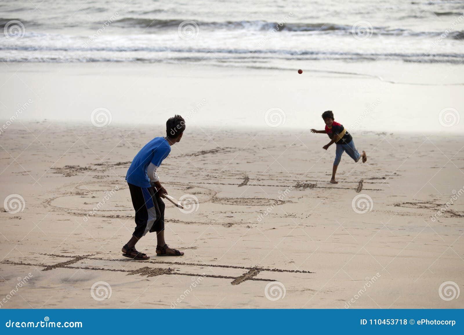 Diveagar Maharashtra, Indien, mars 2013, pojkar som spelar syrsan på stranden