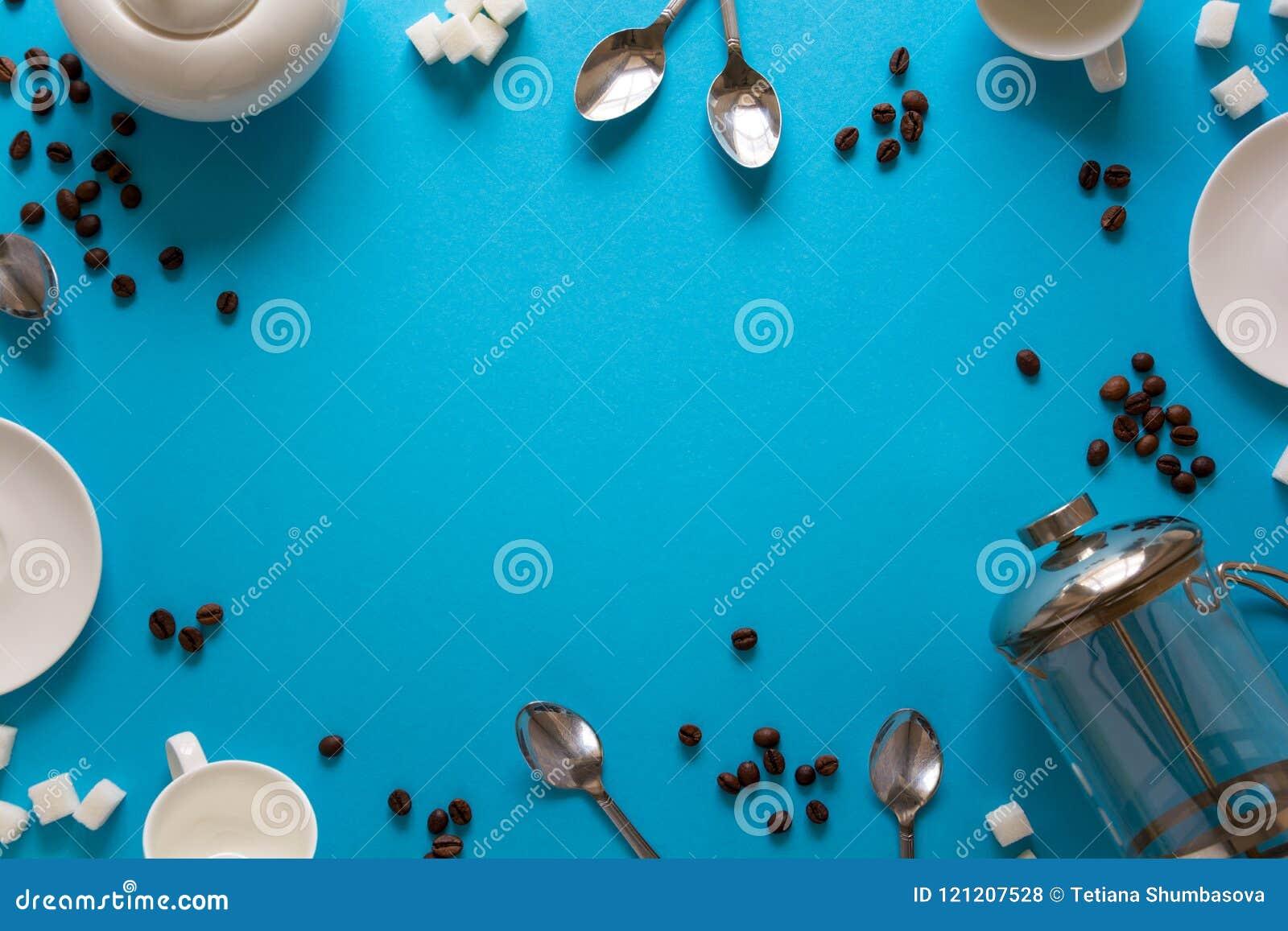 Divers accessoires à café : Presse de café, tasses, soucoupes, grains de café, cuillères et sucre français sur le fond de papier