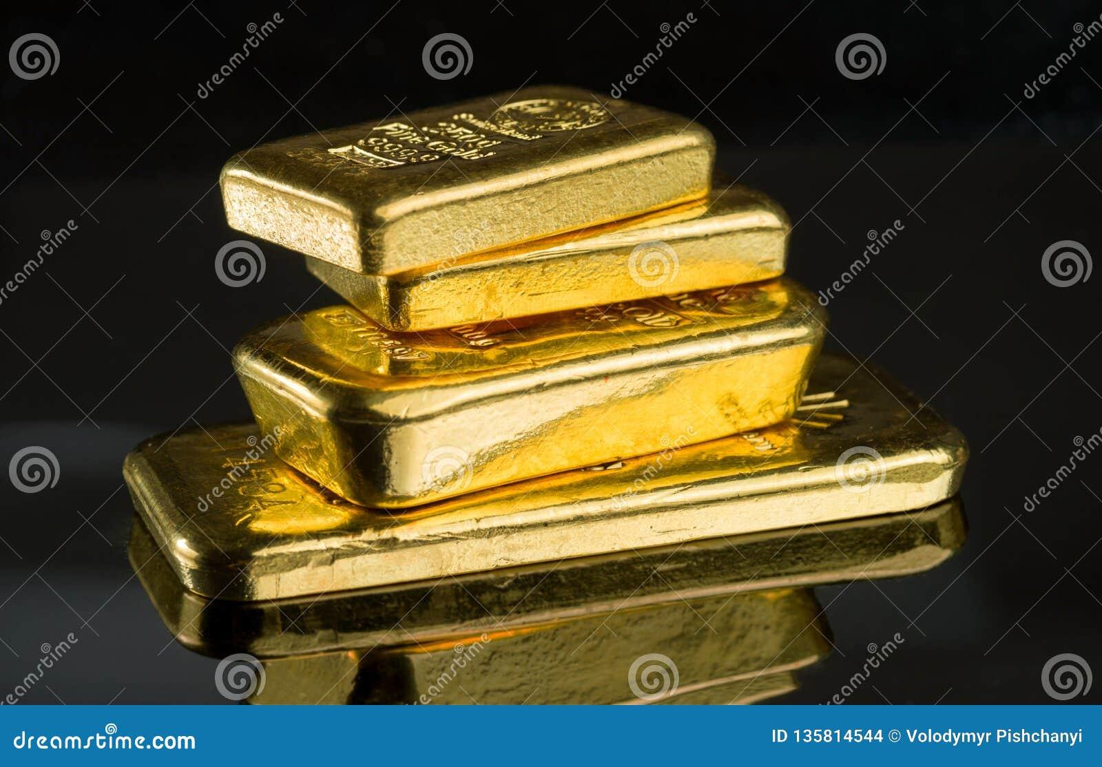 Diversas barras de ouro do peso diferente em uma superfície escura do espelho