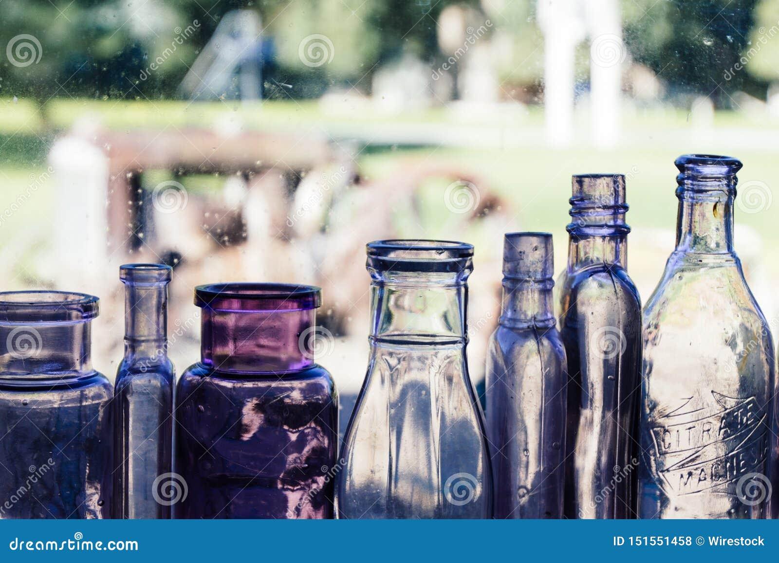 Diversas botellas de cristal clasificadas en fila con el fondo borroso