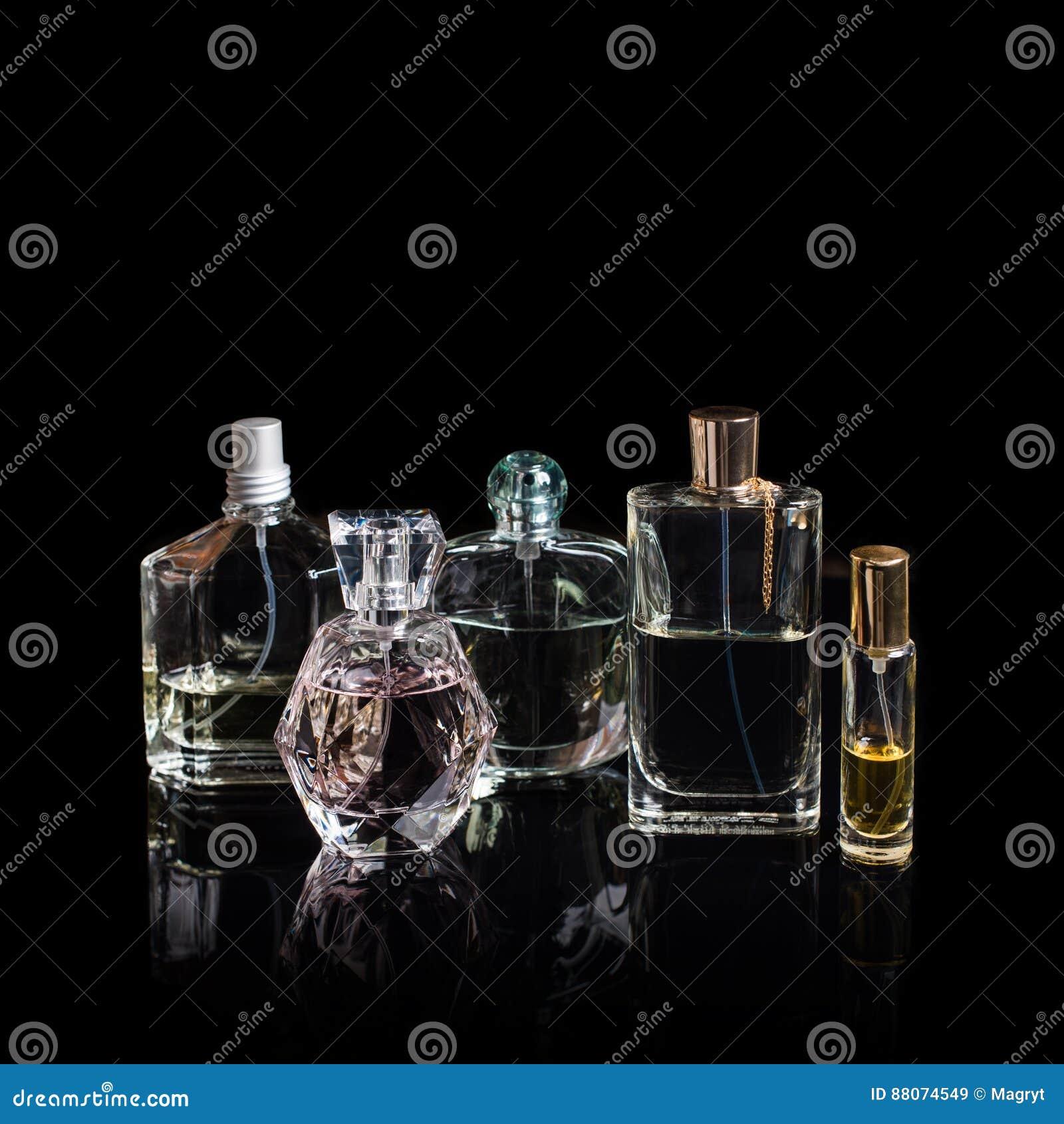 Diversas botellas de perfume con reflexiones en fondo negro con el espacio para el texto Perfumería, cosméticos, fragancia