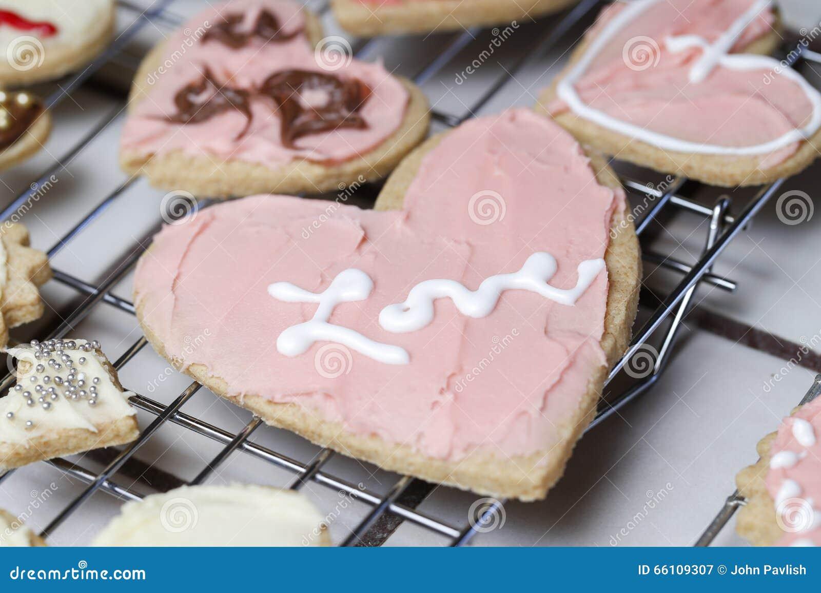 Diversas cookies do feriado do Valentim do coração na geada cor-de-rosa com sobre