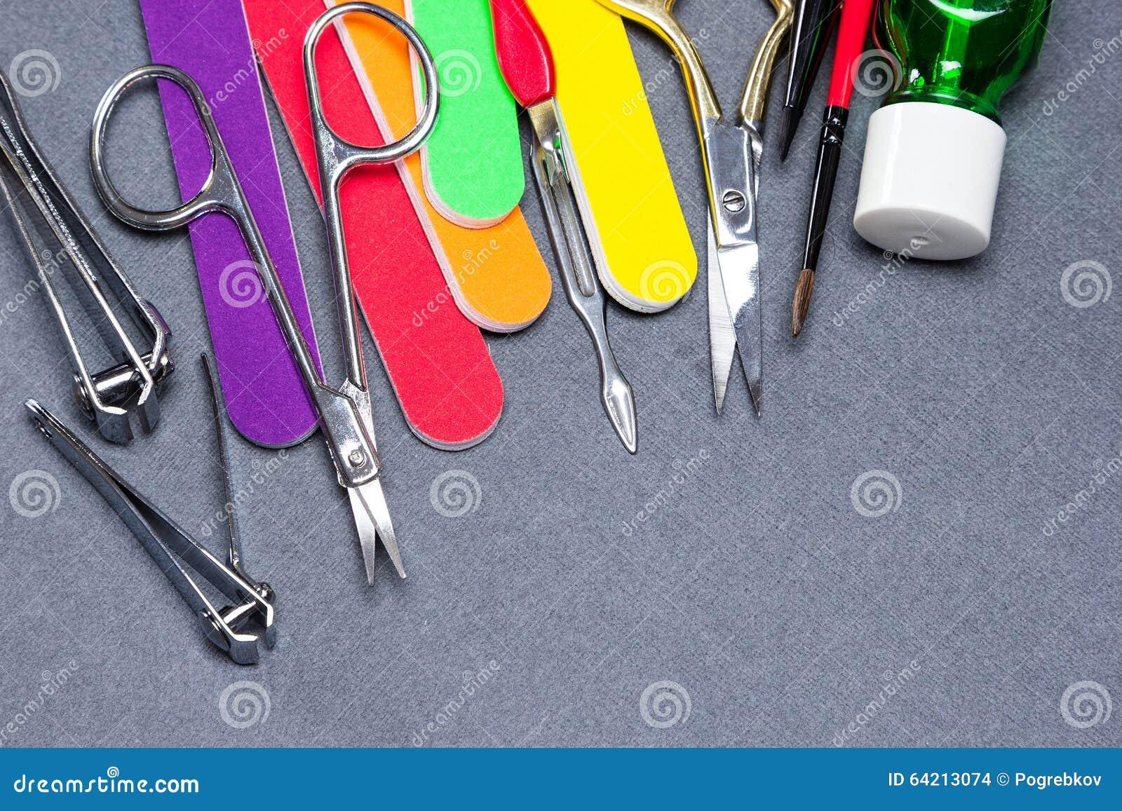 Diversas herramientas de la manicura en fondo texturizado gris