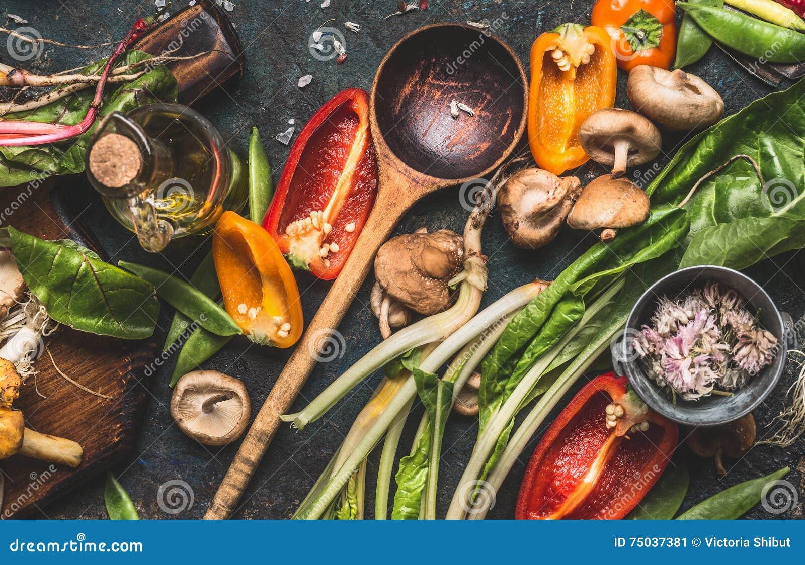 Diversas verduras frescas con la cuchara de cocinar de madera para la consumición y la nutrición sanas en fondo rústico oscuro