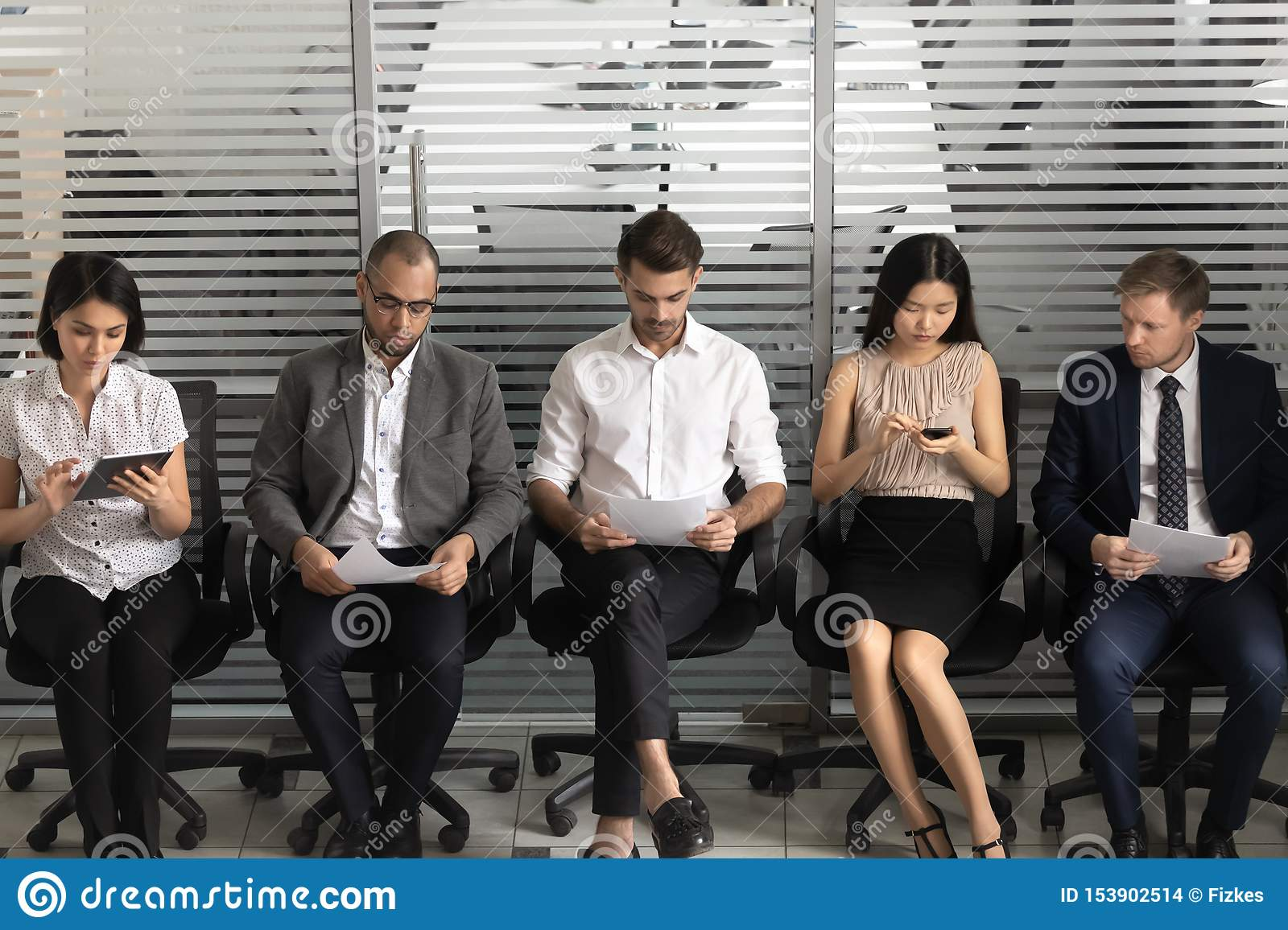 Diverse applicants sit on chairs in row in waiting room