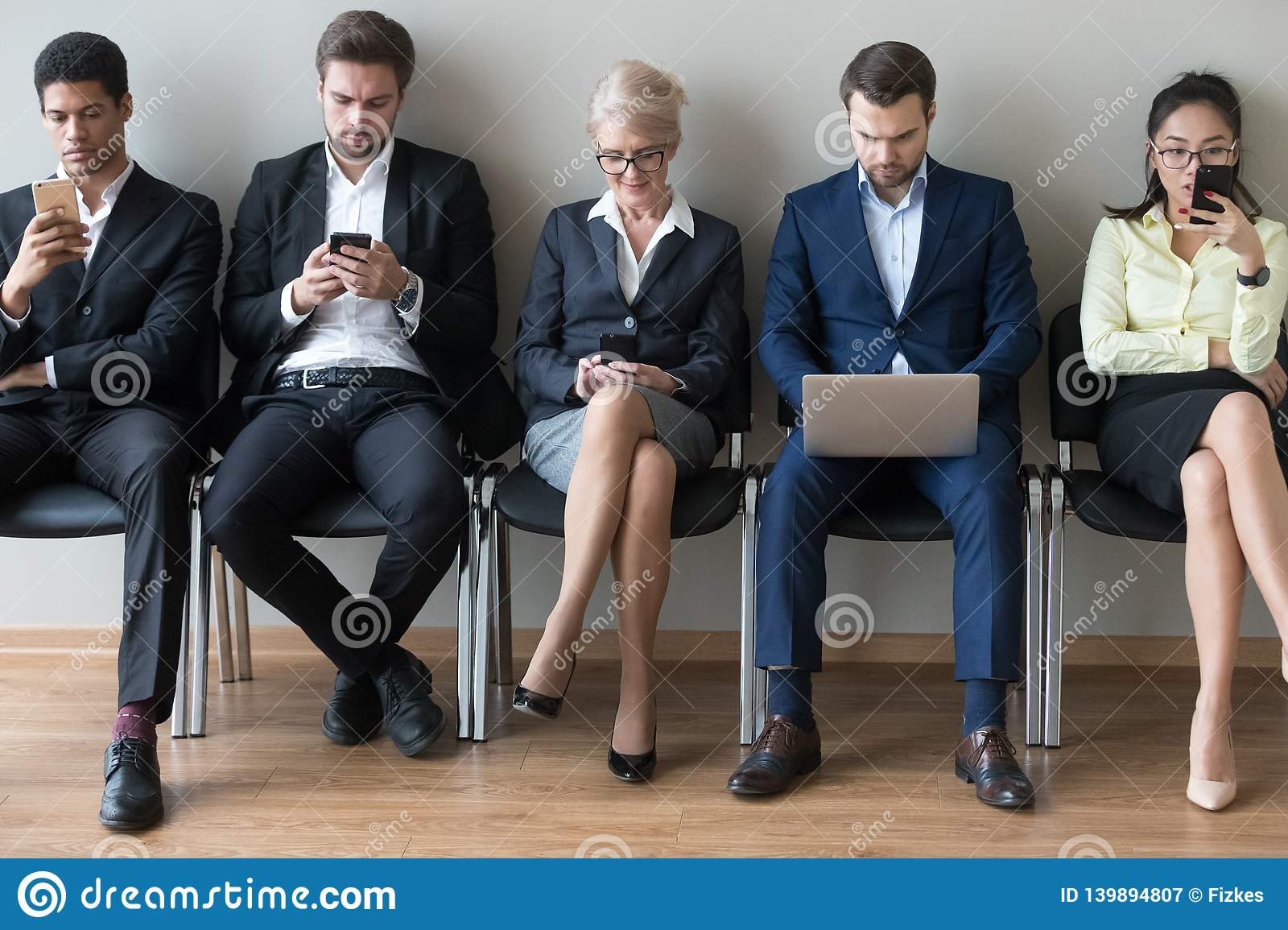Diverse businesspeople sitting in row using devices phones and laptop