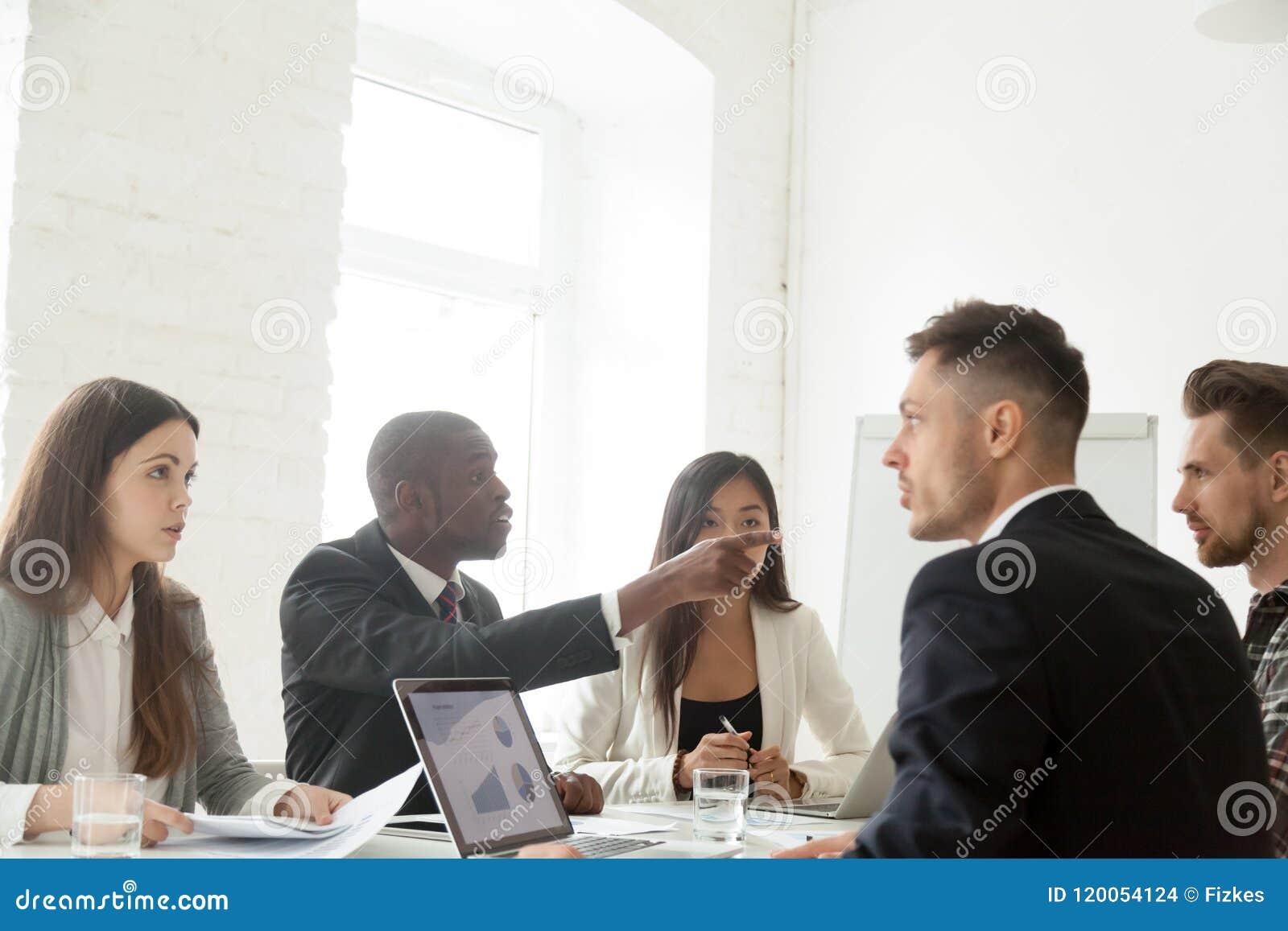 Diverse colleagues disputing during work meeting