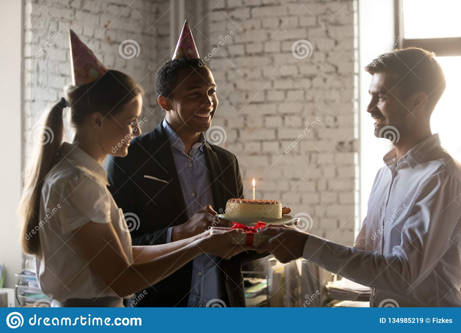 Diverse Employees In Party Hats Holding Giving Cake Gift Box Congratulating Coworker Receiving Happy Birthday Present Friendly Workers Make Surprise To