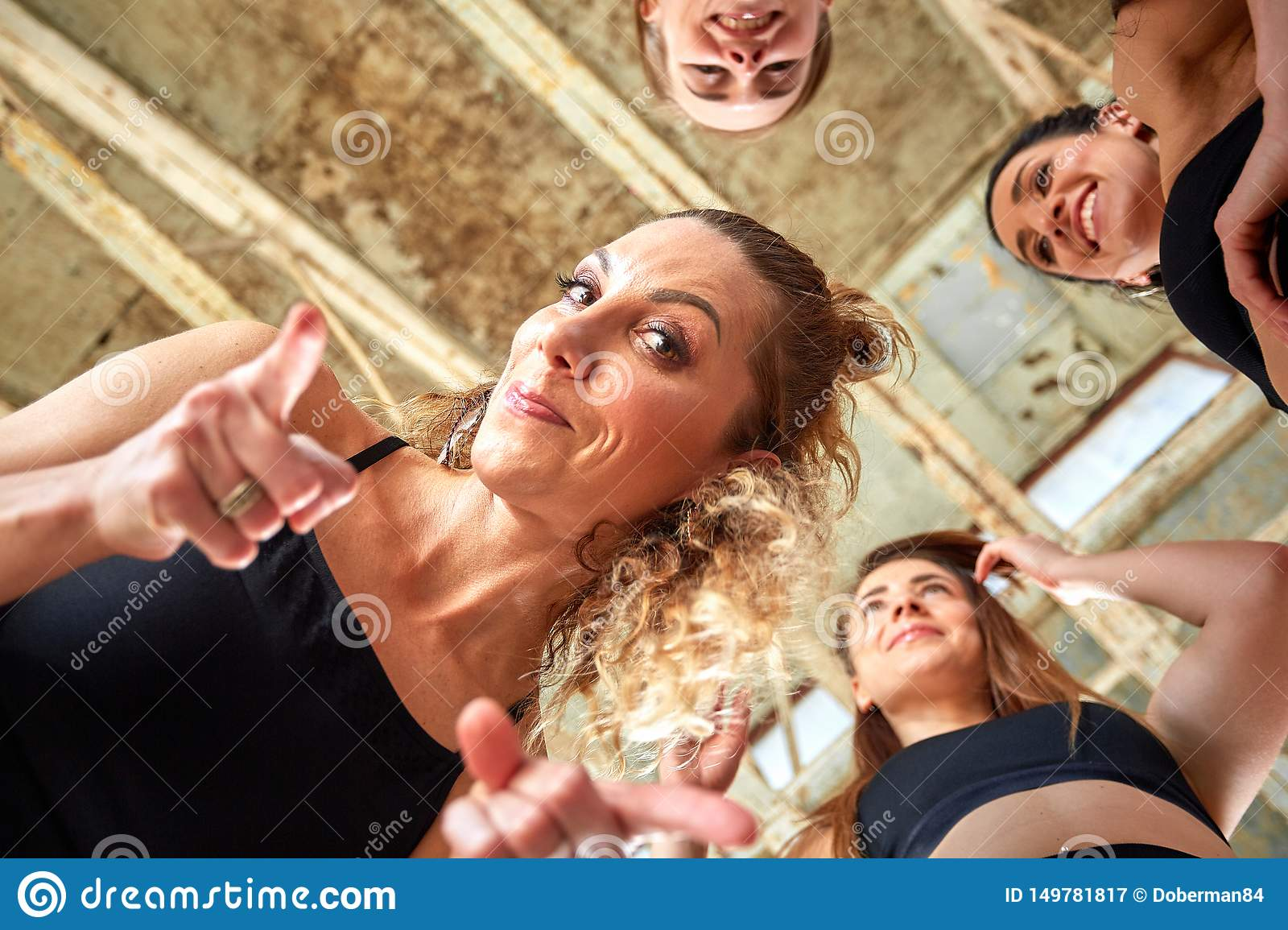 Diverse funny girls together in circle on rubber mats wearing sportswear smiling show yoga greeting gesture, looking at