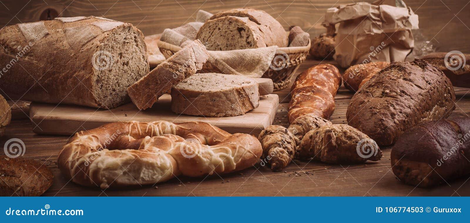 Diverse gebakken broden en broodjes op rustieke houten lijst