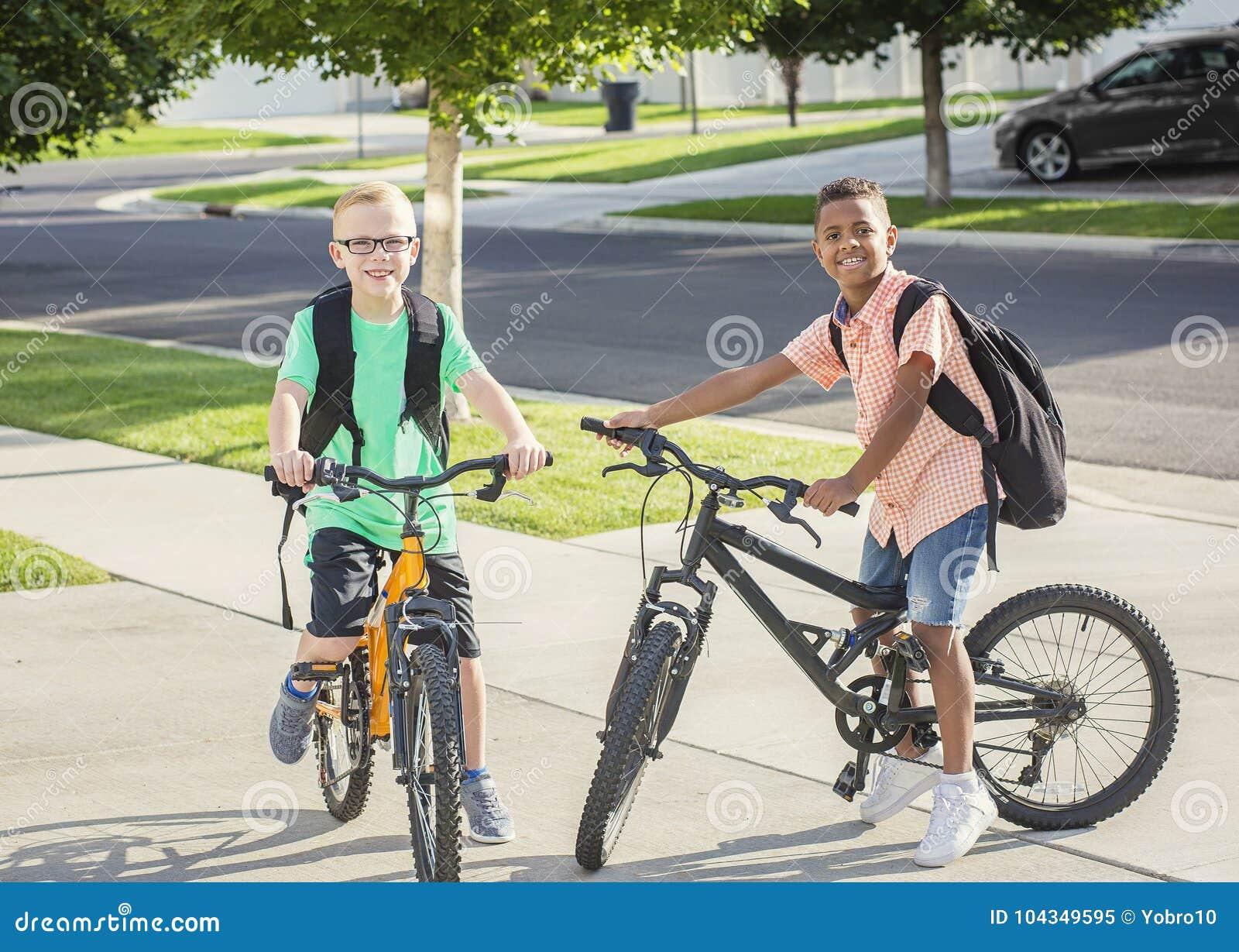 Diverse groep die jonge geitjes hun fietsen samen berijden aan school