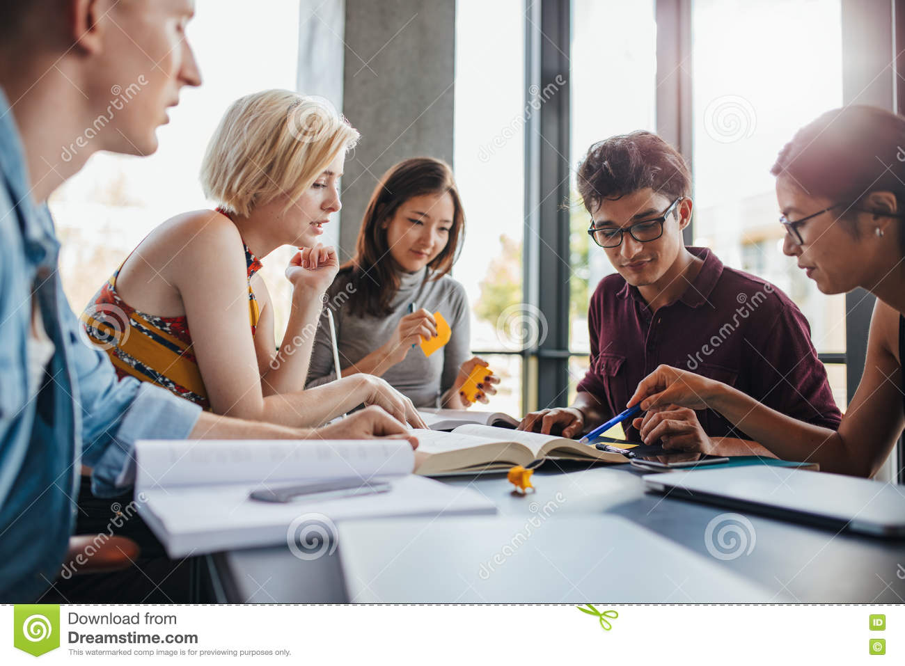 Diverse group of students studying at library stock photo - One of your students left their book on the table ...
