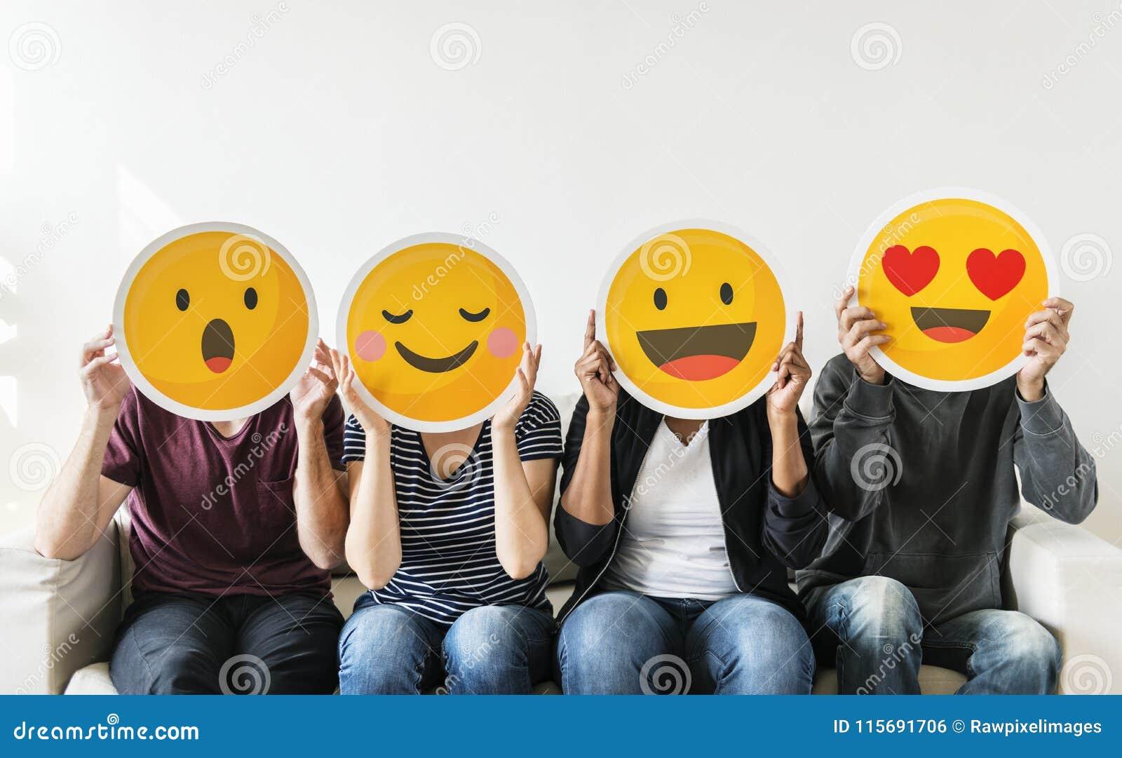 Diverse jongeren die emoticon houden